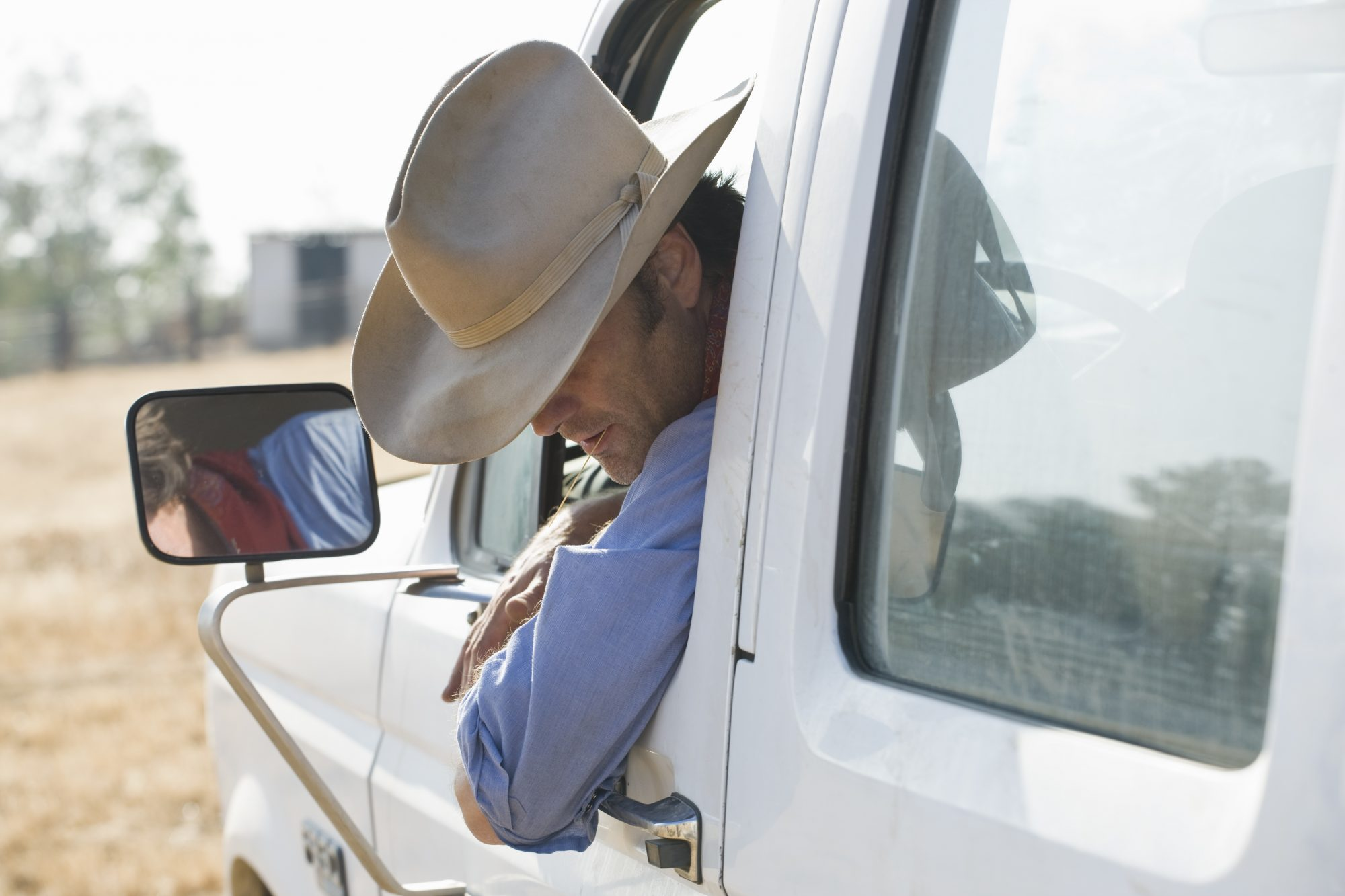 A man leaning out of his truck and looking down