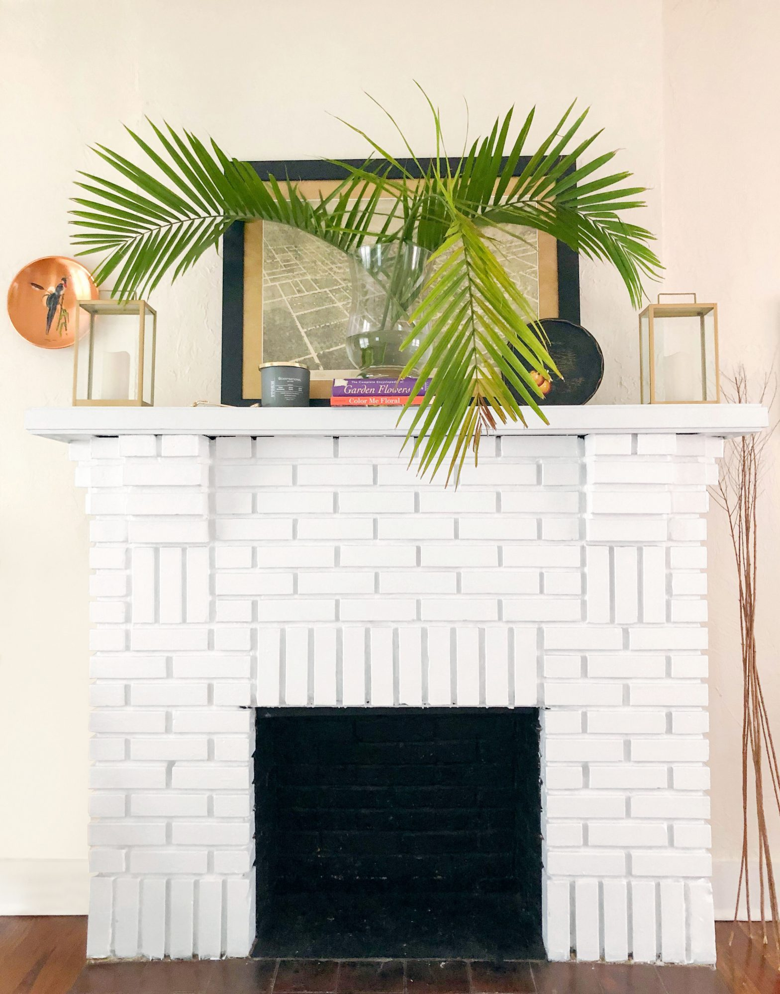 White fireplace with lanterns, map artwork, and palm fronds