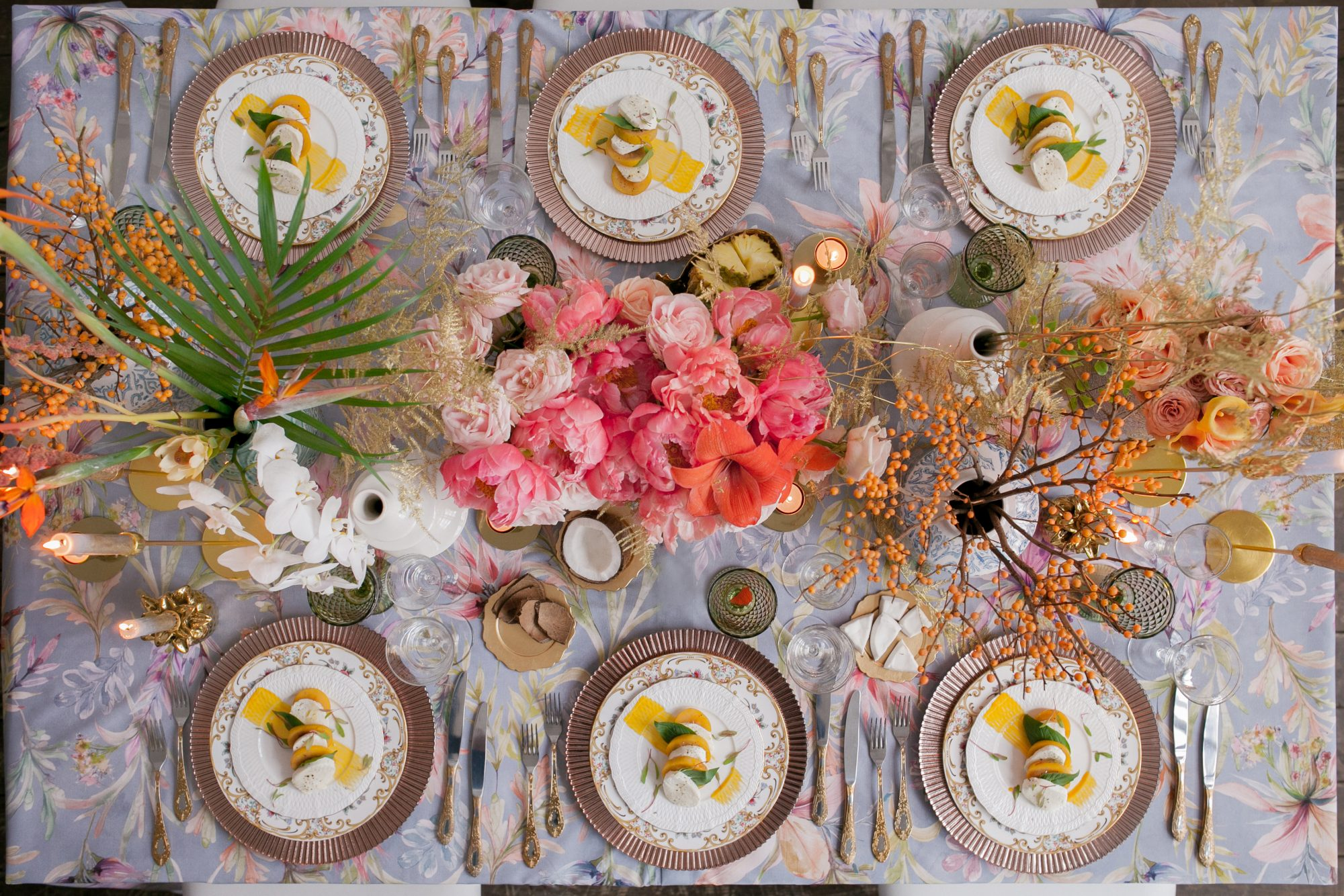 Festive table decor. Many pastel colors. Luxury wedding, party, birthday. Copper chairs and dishes, gold, silver cutlery. Chinese, European, chinoiserie style. candle, mozzarella, persimmons. Above.