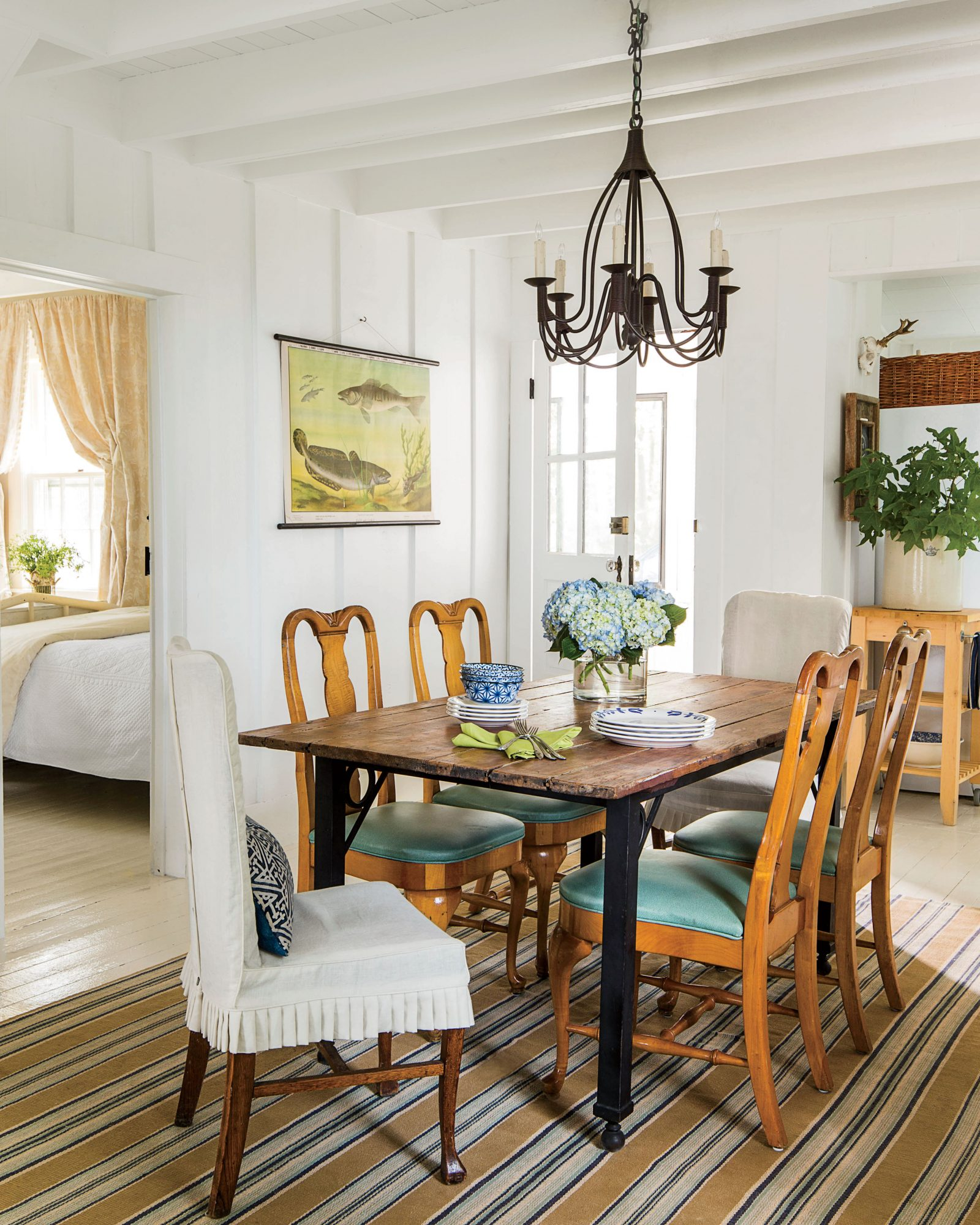 River House dining area with white painted walls and wood and iron dining table