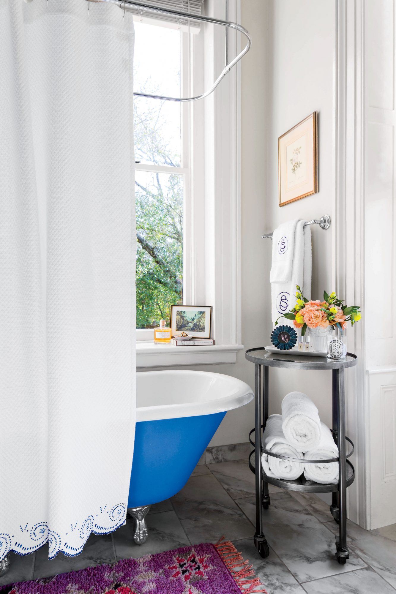 White bathroom with blue clawfoot tub and white shower curtain