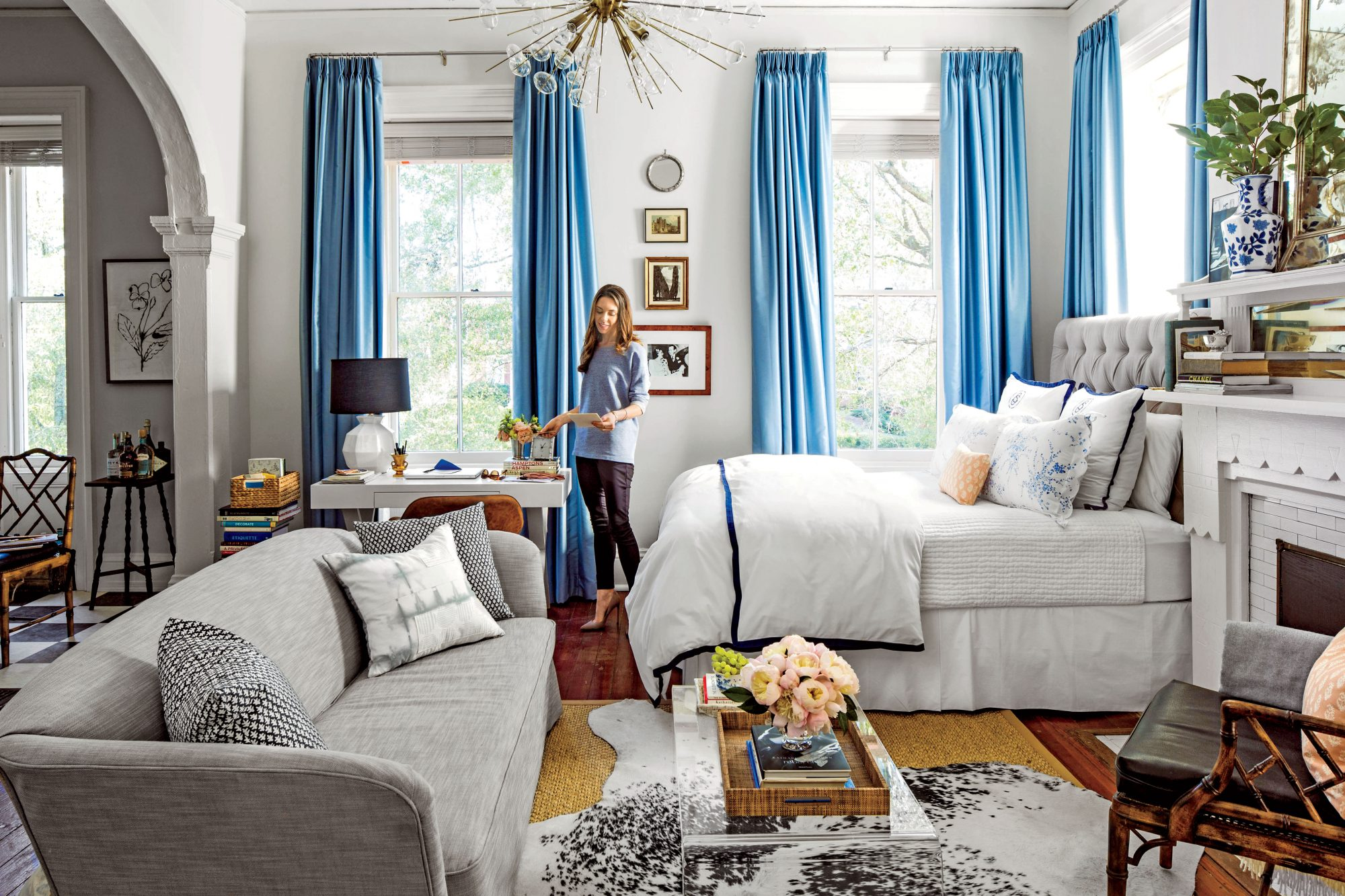 Studio apartment living room and bed with white walls and blue accents