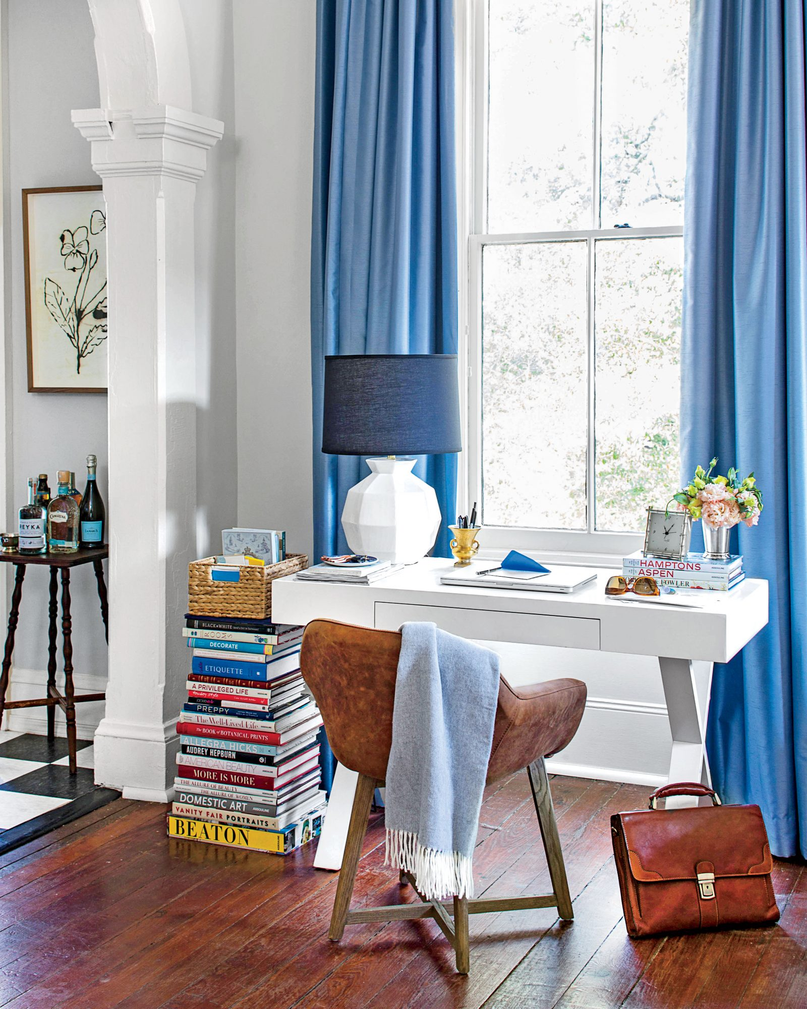 White desk with stack of books as side table