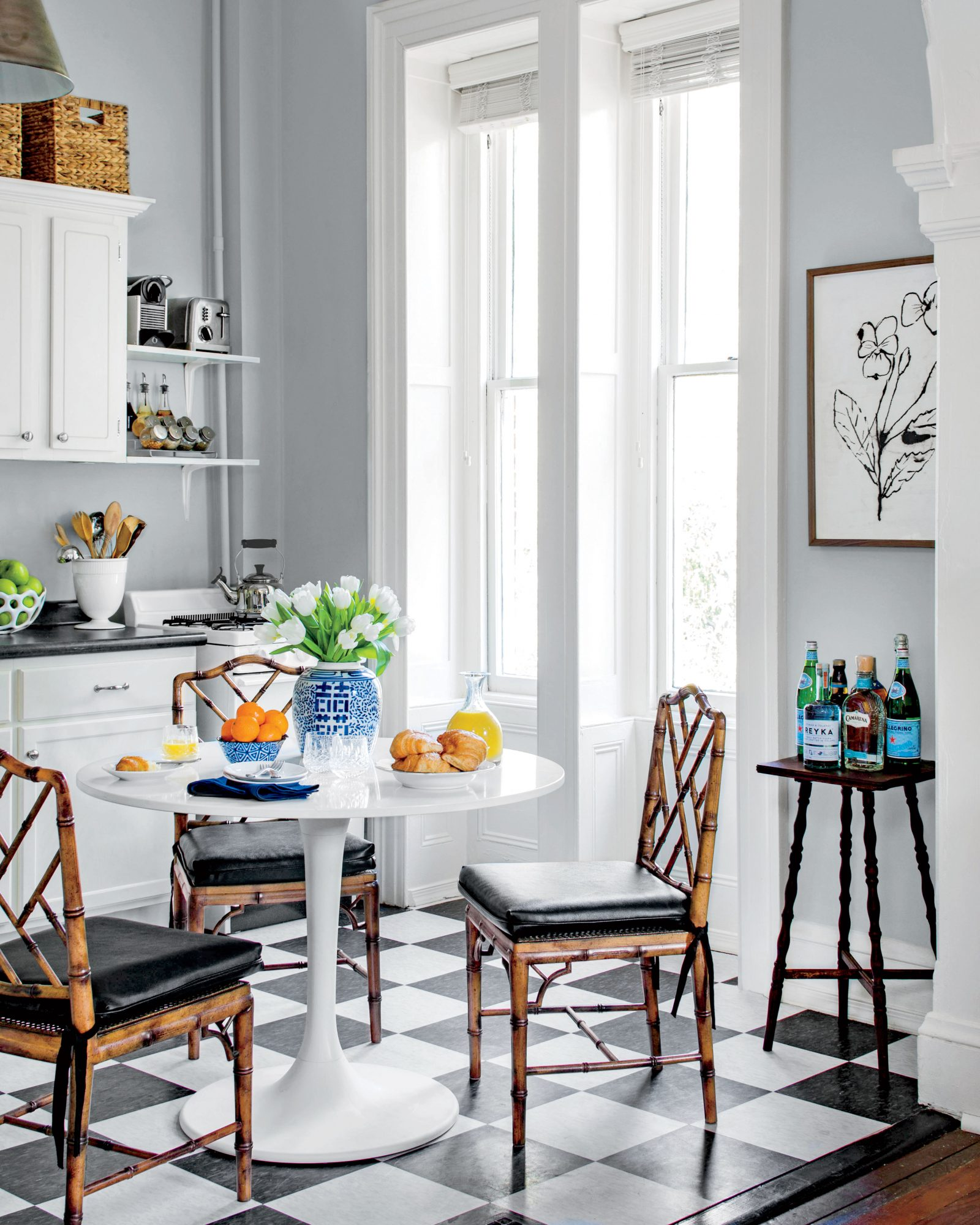 Small apartment kitchen with black and white tile floors and white tulip table for seating