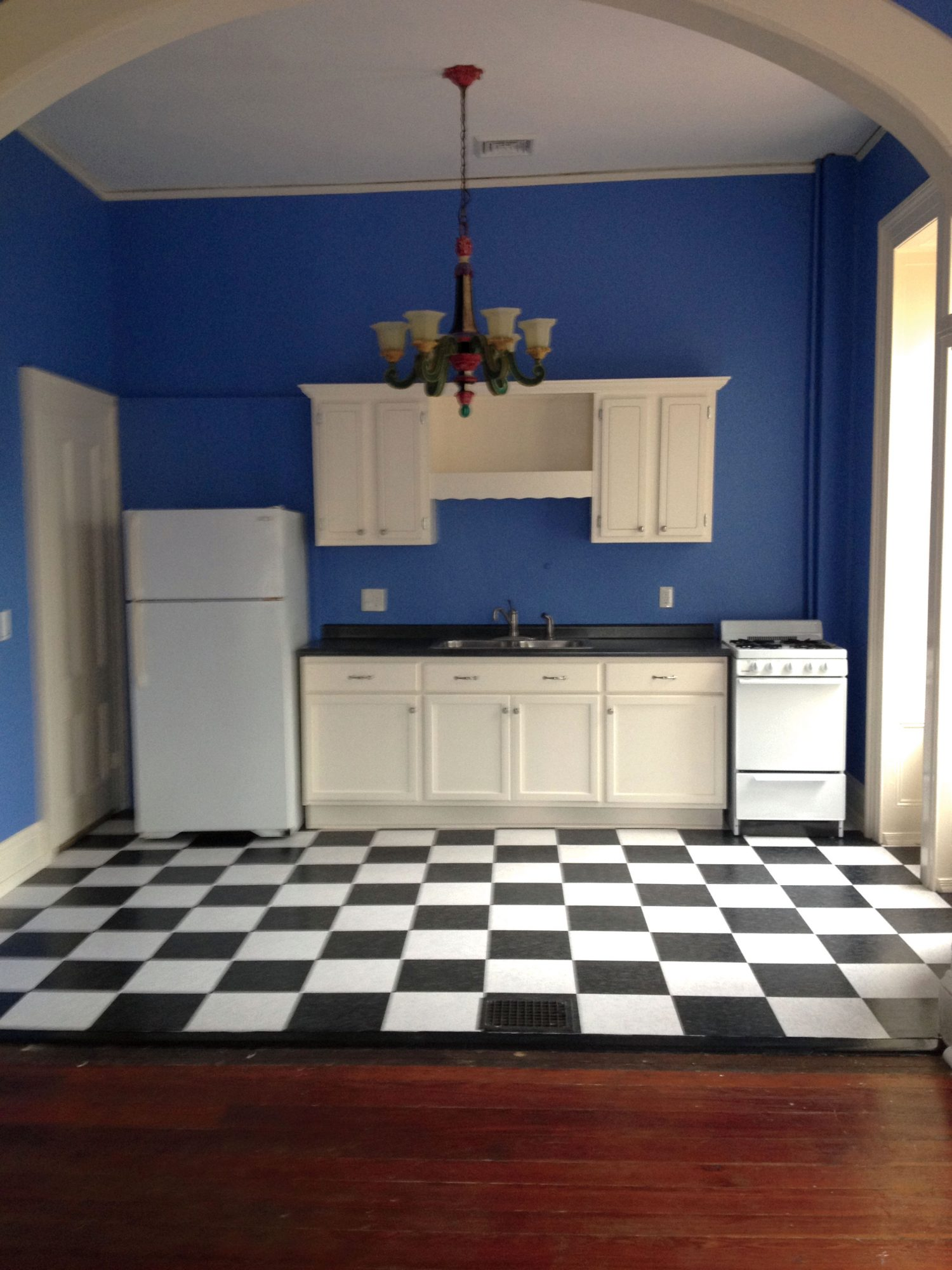 Studio apartment kitchen before with blue walls and black and white tile floor