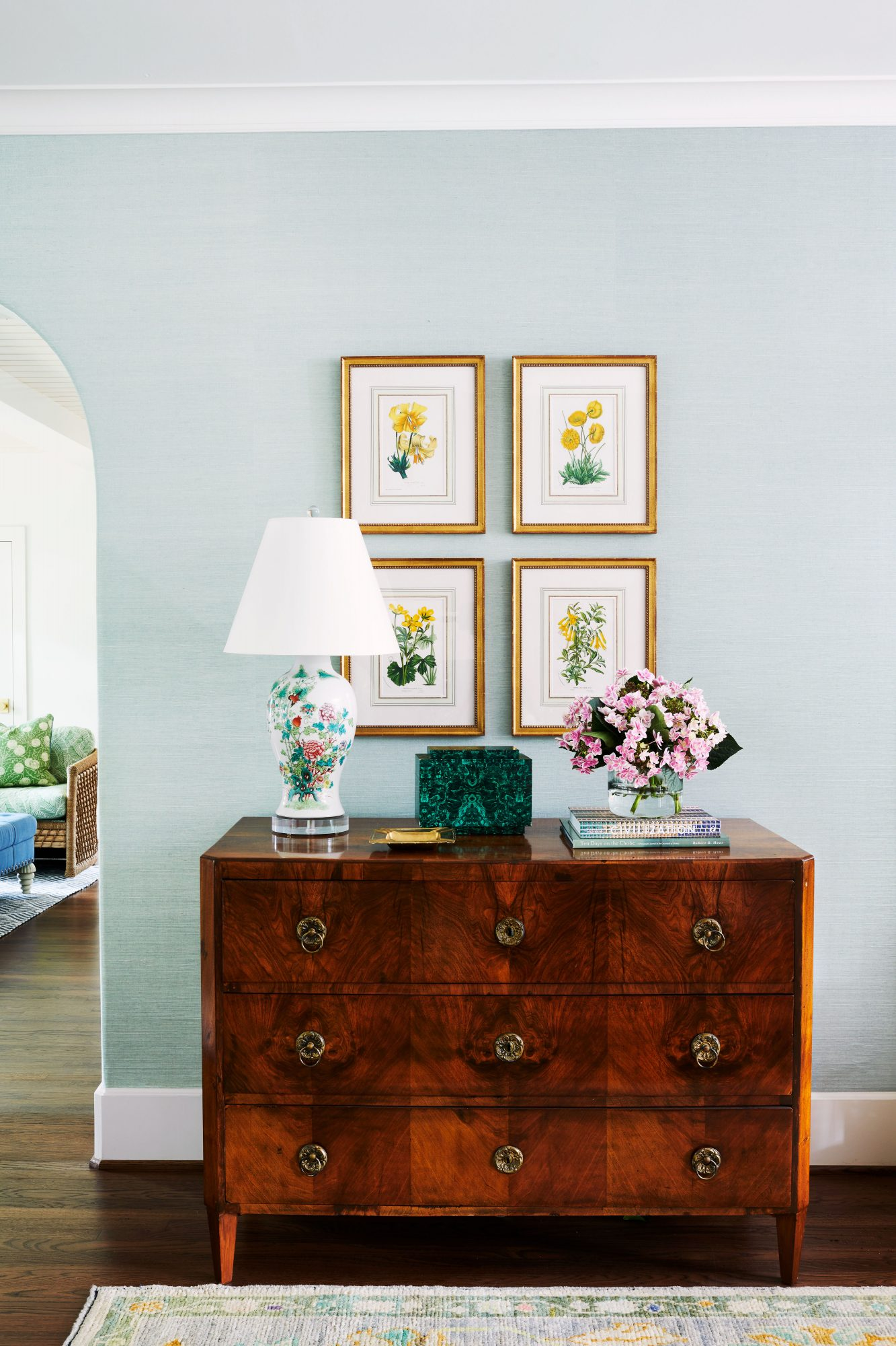 Light blue wall room with antique dresser and botanical prints hung above