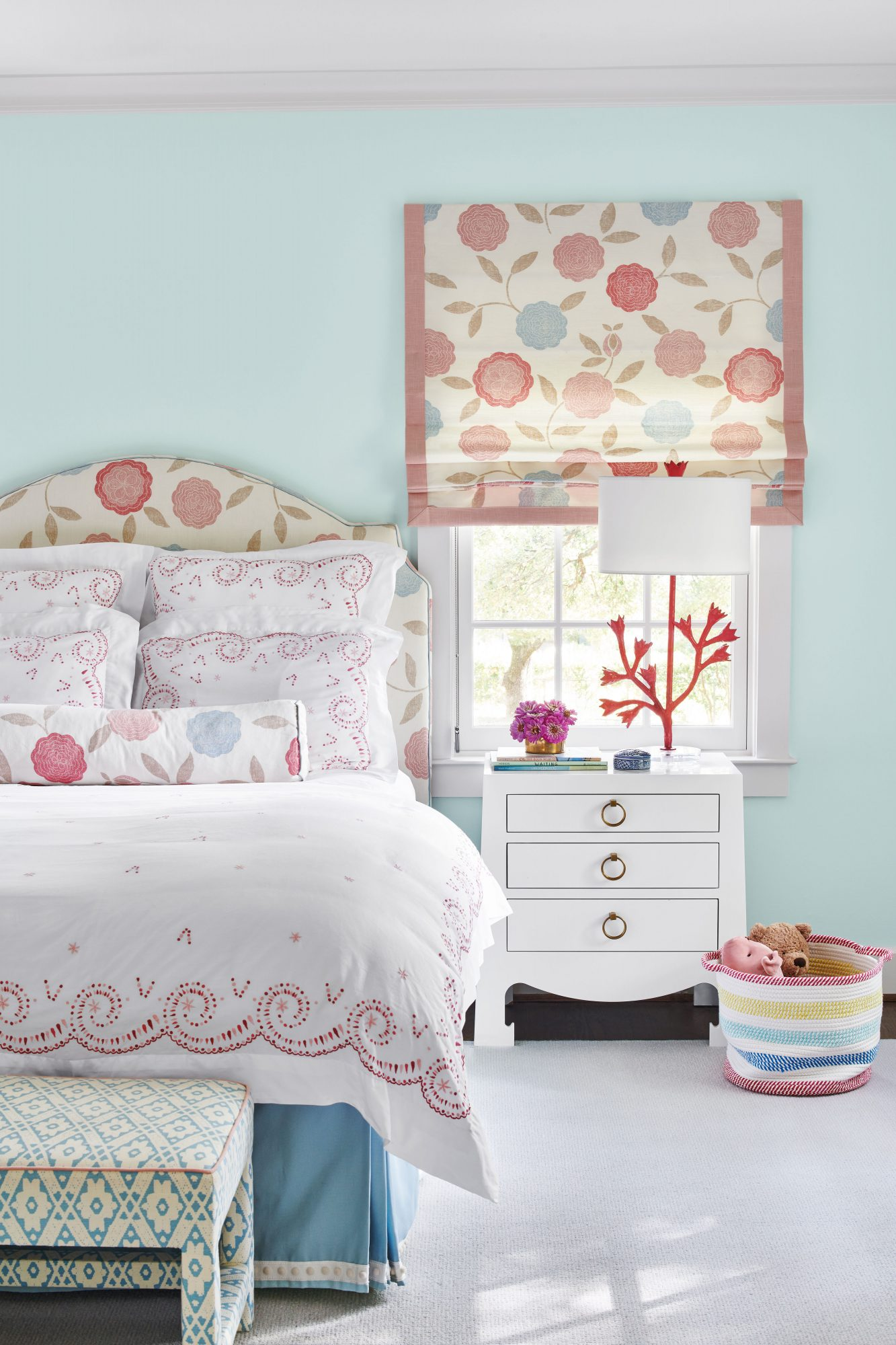 Girls bedroom with light blue walls and pops of pink in accent fabrics