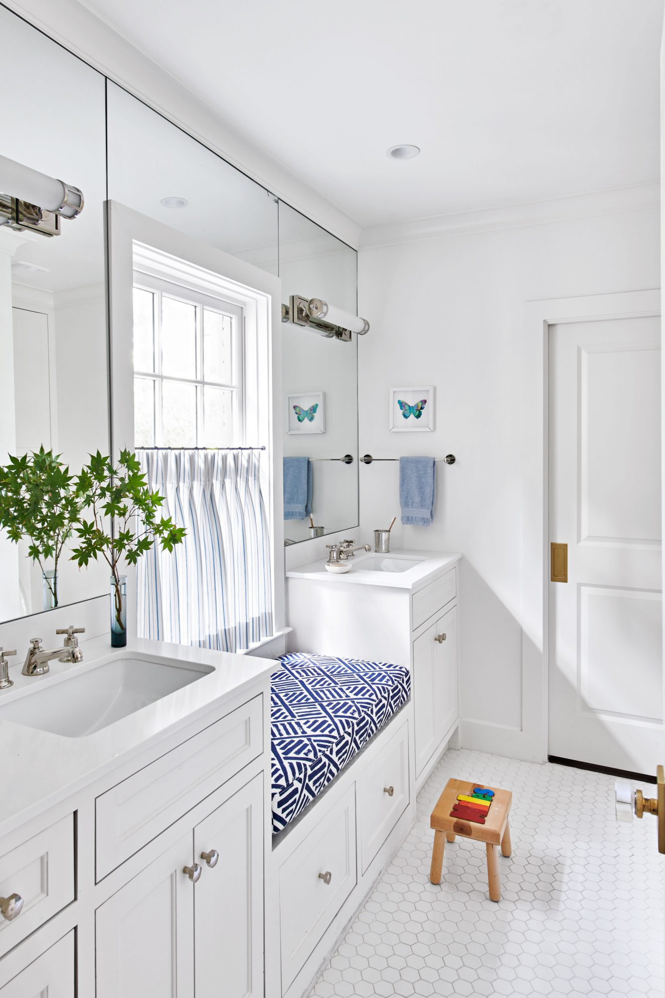 White bathroom with blue window seat between sinks
