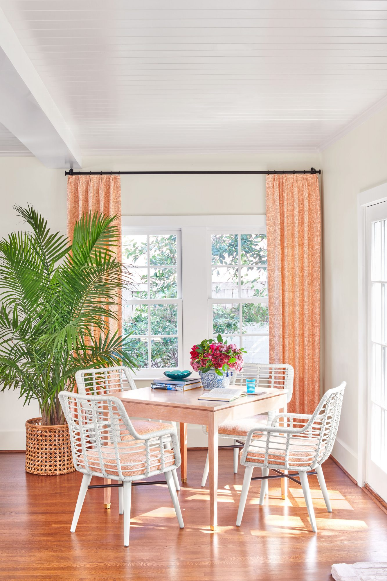 Card table in white room with orange curtains and white chairs
