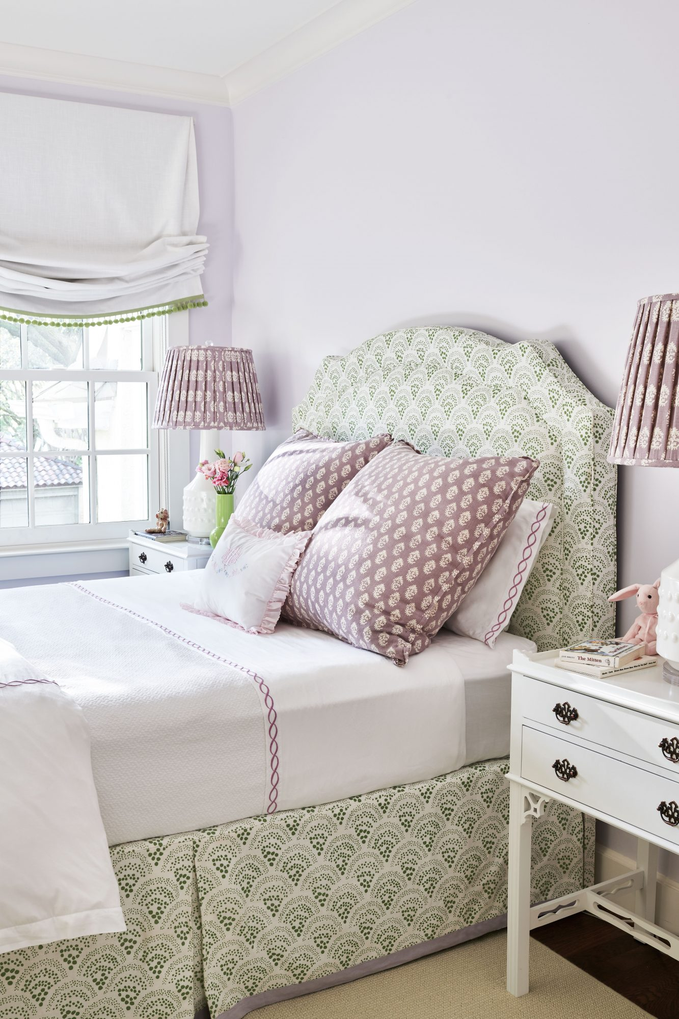 Girls bedroom with purple walls, pillows, and lampshade against a green fabric headboard