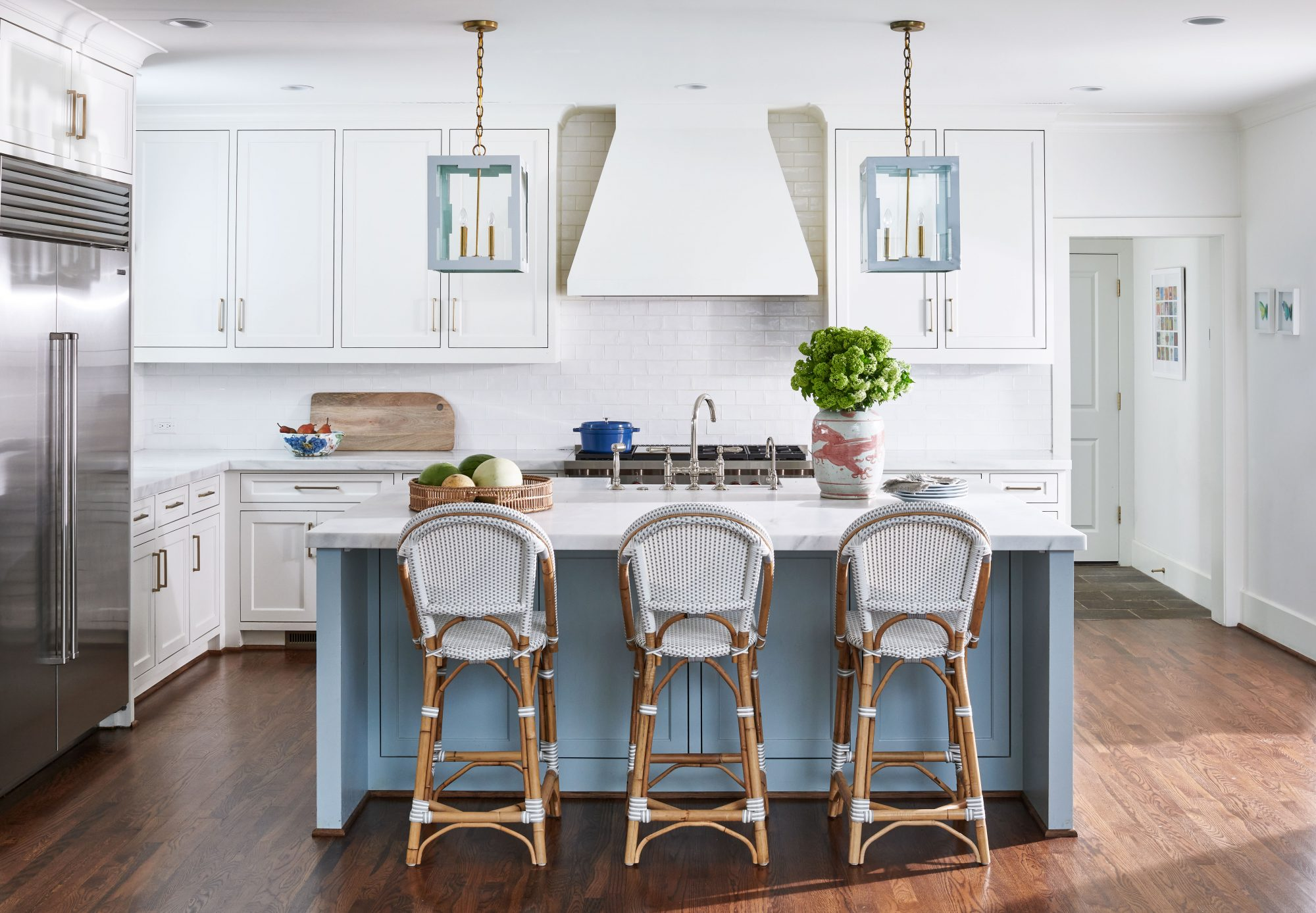 White kitchen with blue island and blue lanterns