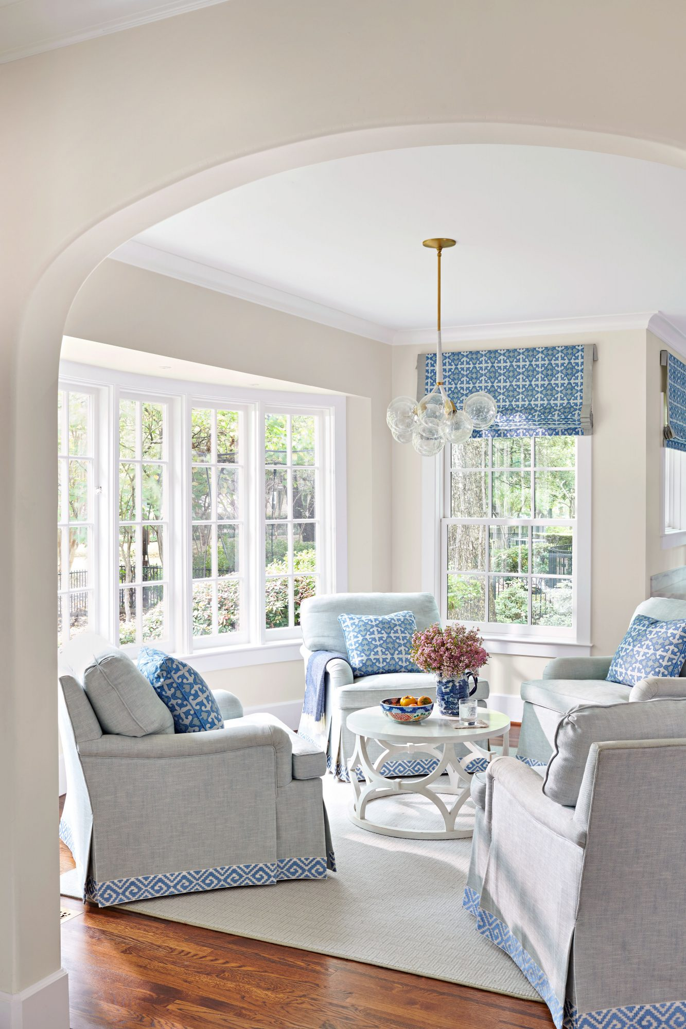 Sitting area with white walls and four arm chairs with blue accents