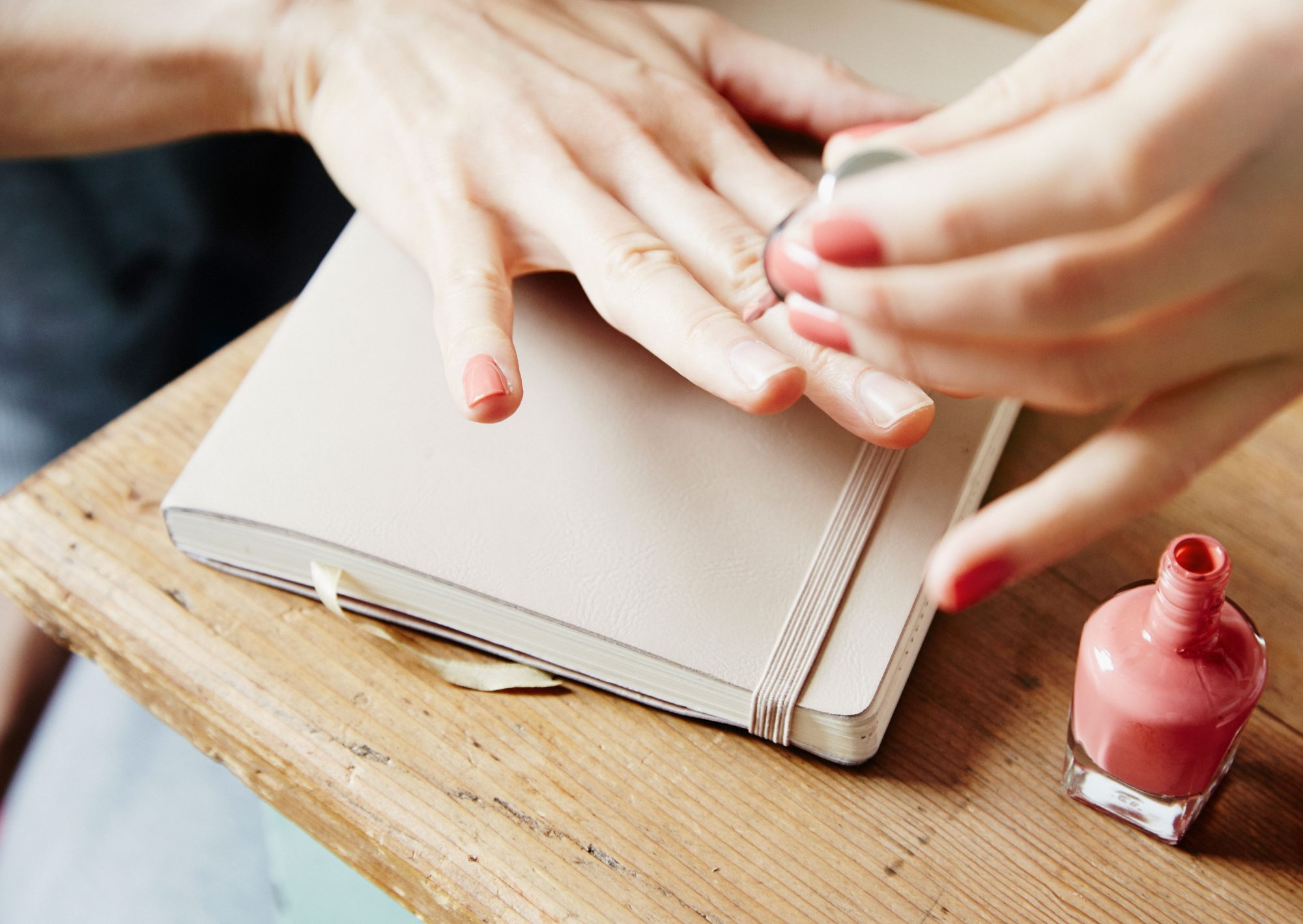 Woman Painting Nails on Top of Notebook and Desk
