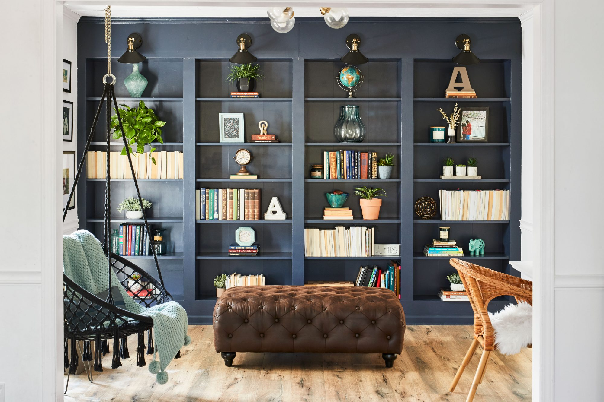 Modern DIY built in bookshelf wall with hanging chair
