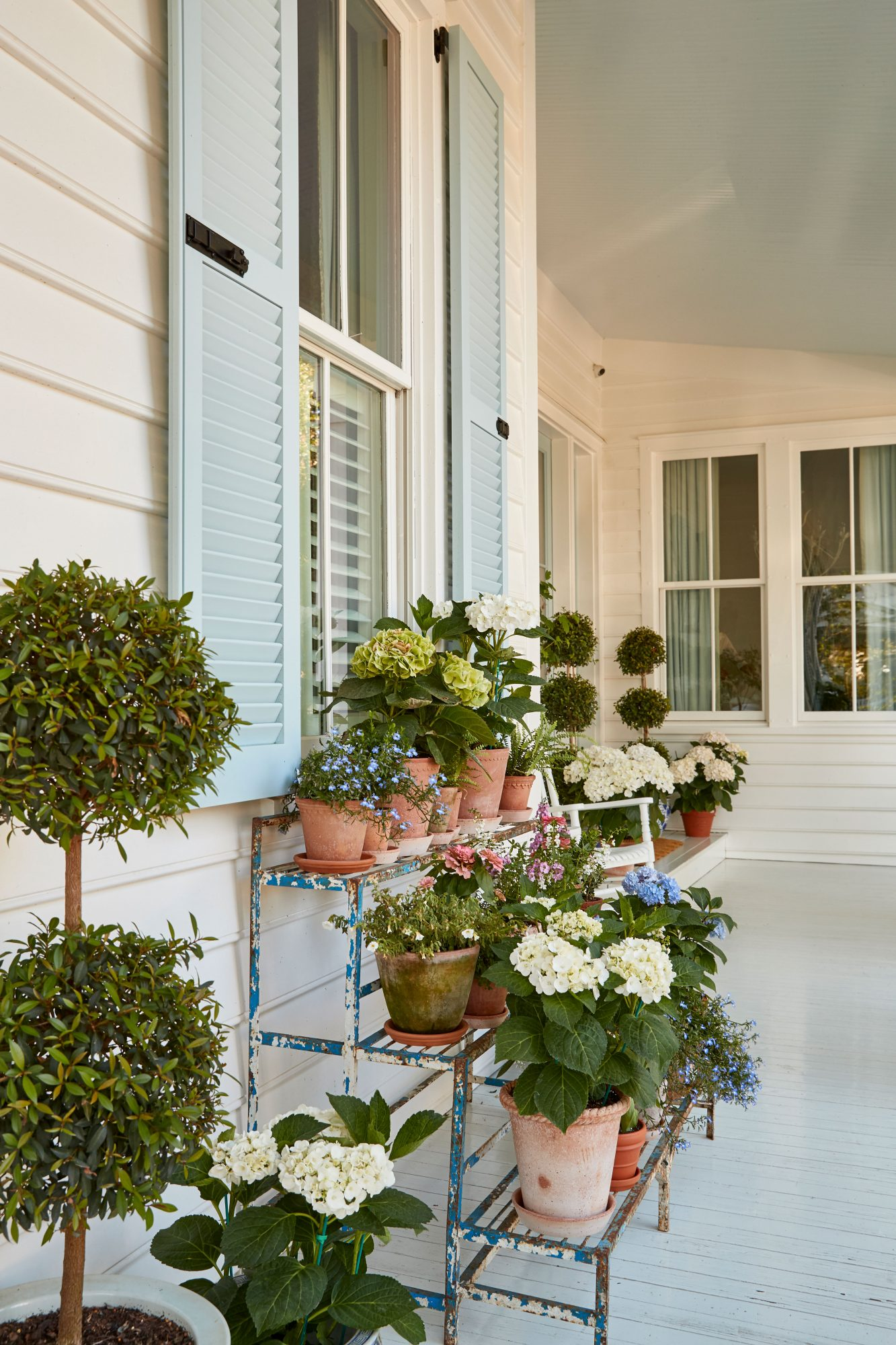 Layered potted plants on front porch