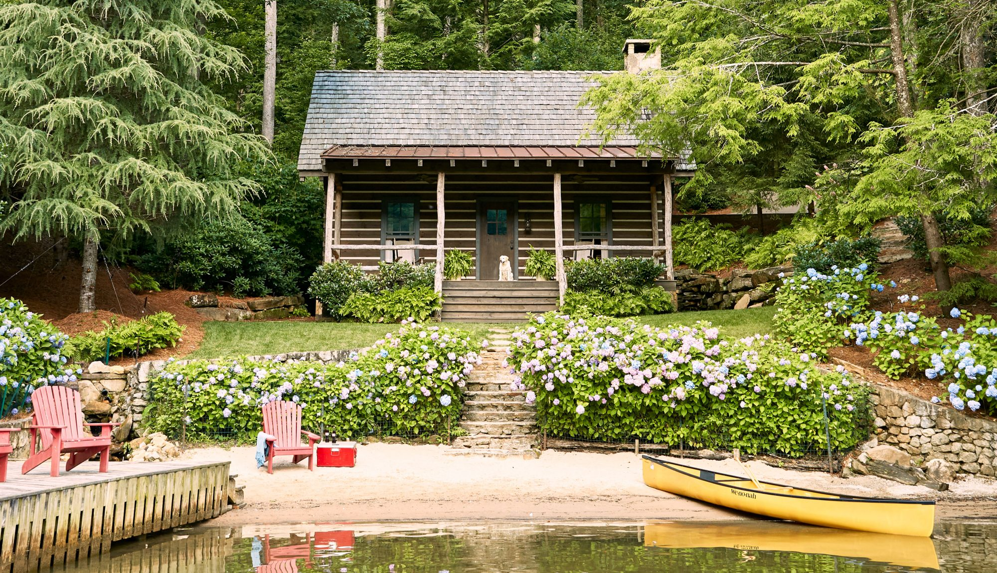 Log cabin on the lake with hydrangea bushes