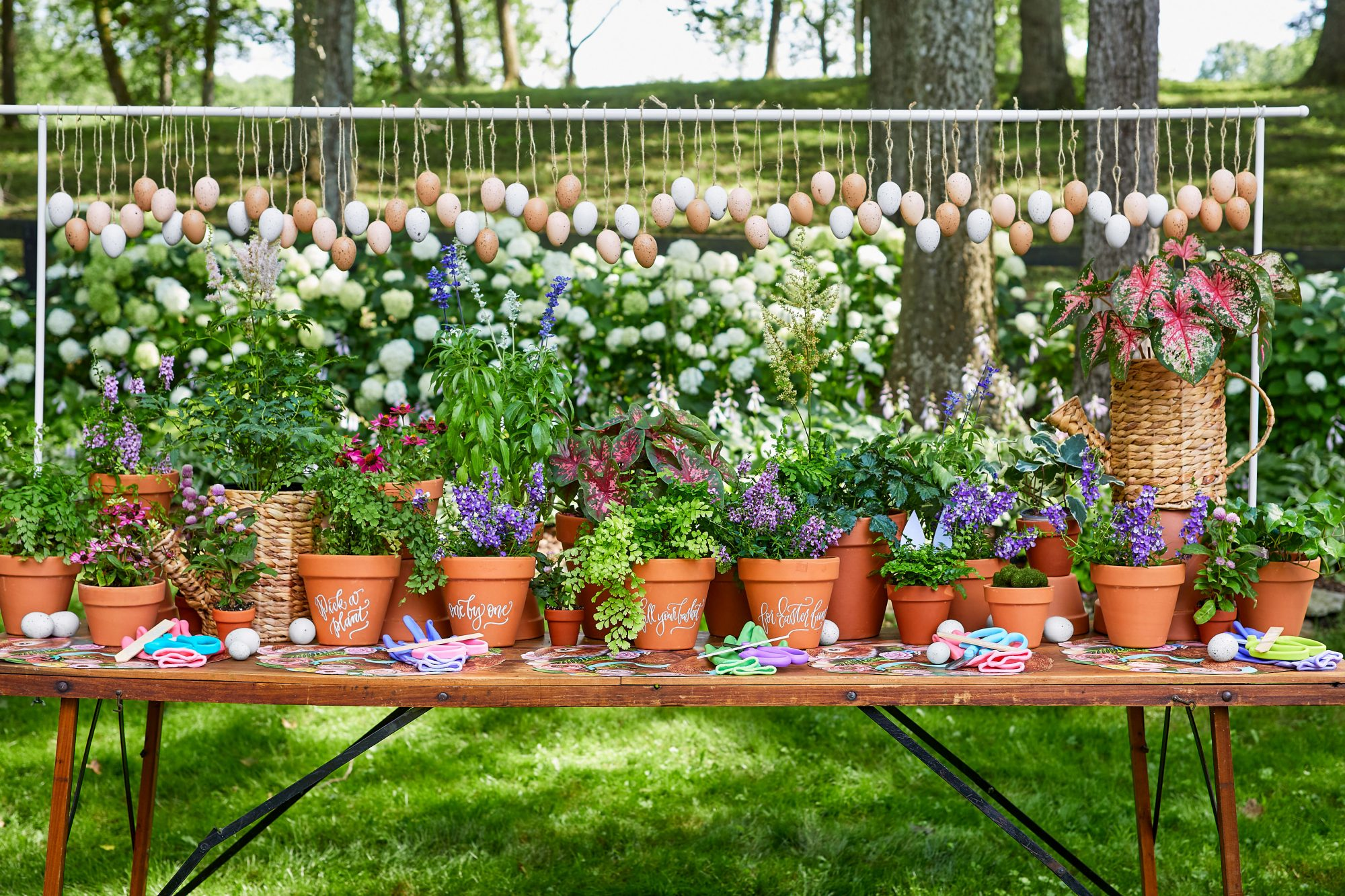 Outdoor Table covered in potted flowers with hanging eggs above