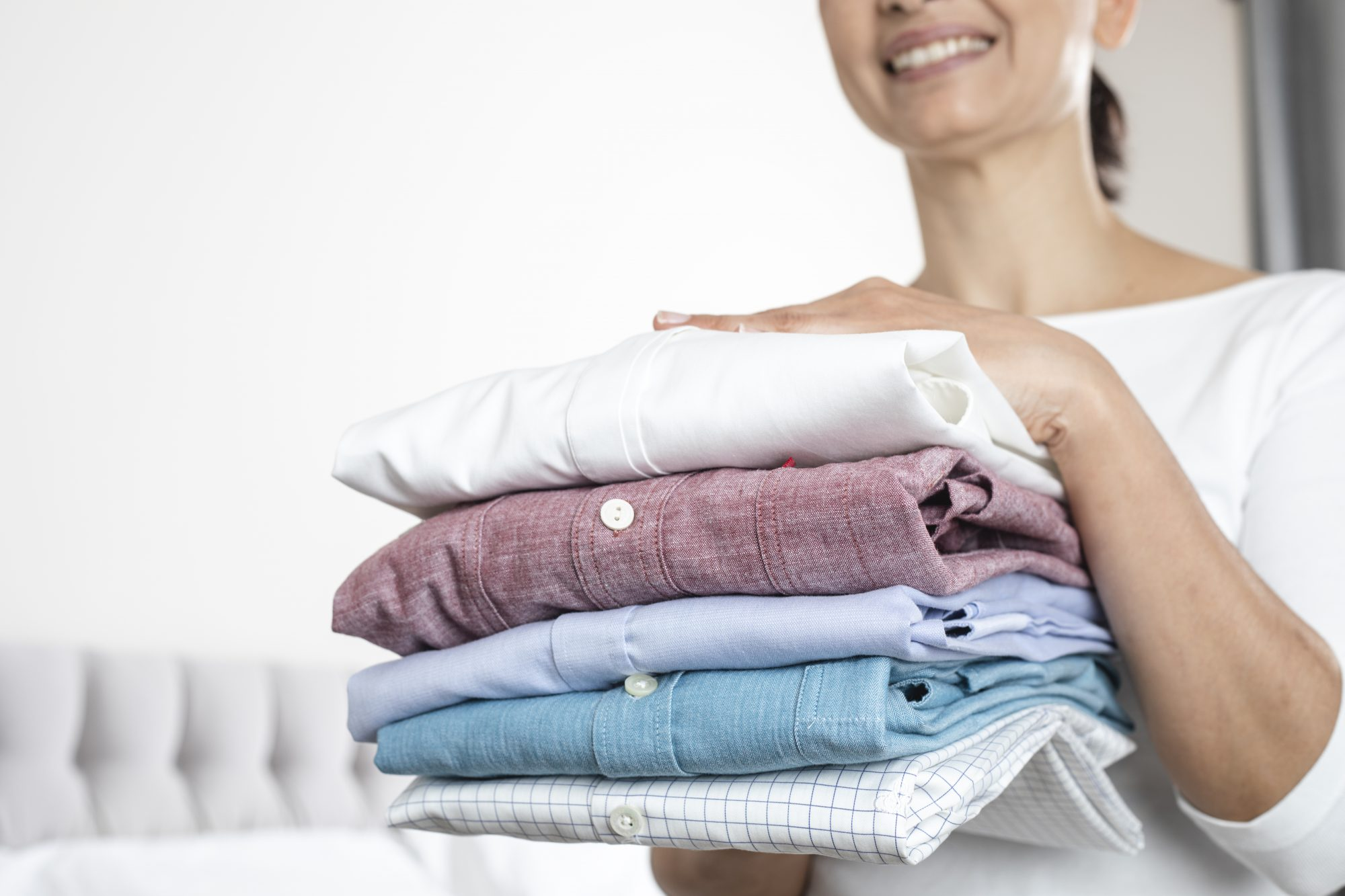 Woman Is Holding a Stack of Ironed and Folded Shirts