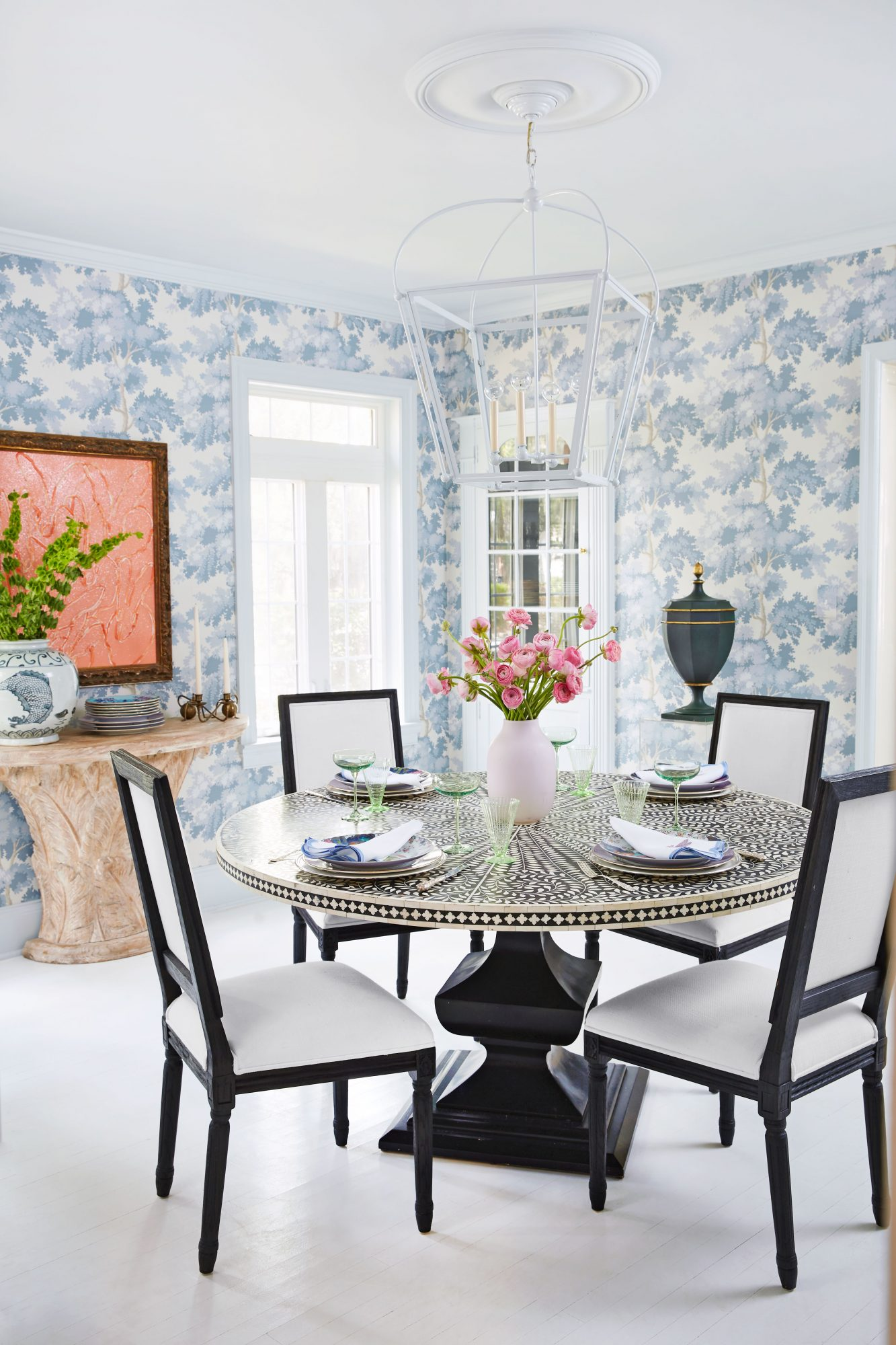 Formal dining room with light blue and white wallpaper, black round dining table, and black and white dining chairs