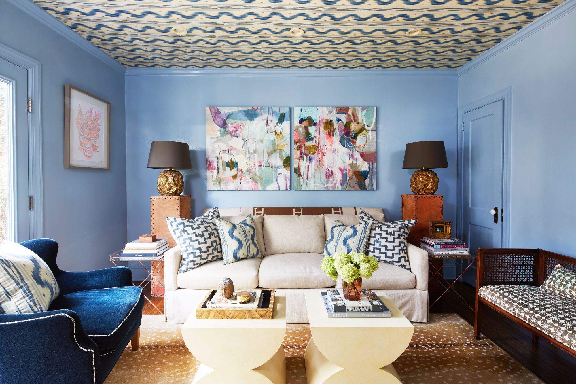Study with light blue walls, wallpapered ceiling, and white sofa