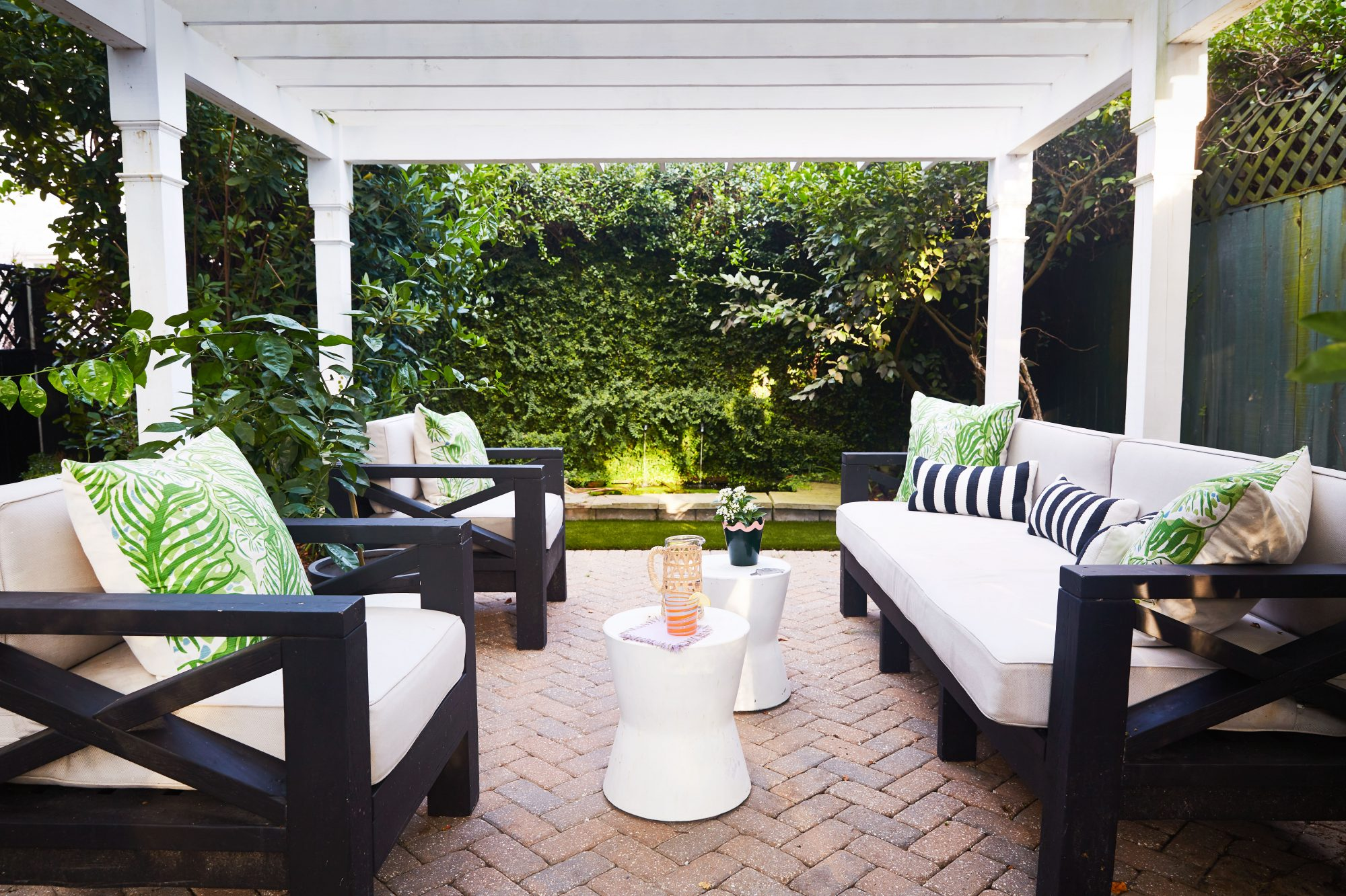 Pergola-covered patio with outdoor seating and adjacent koi pond