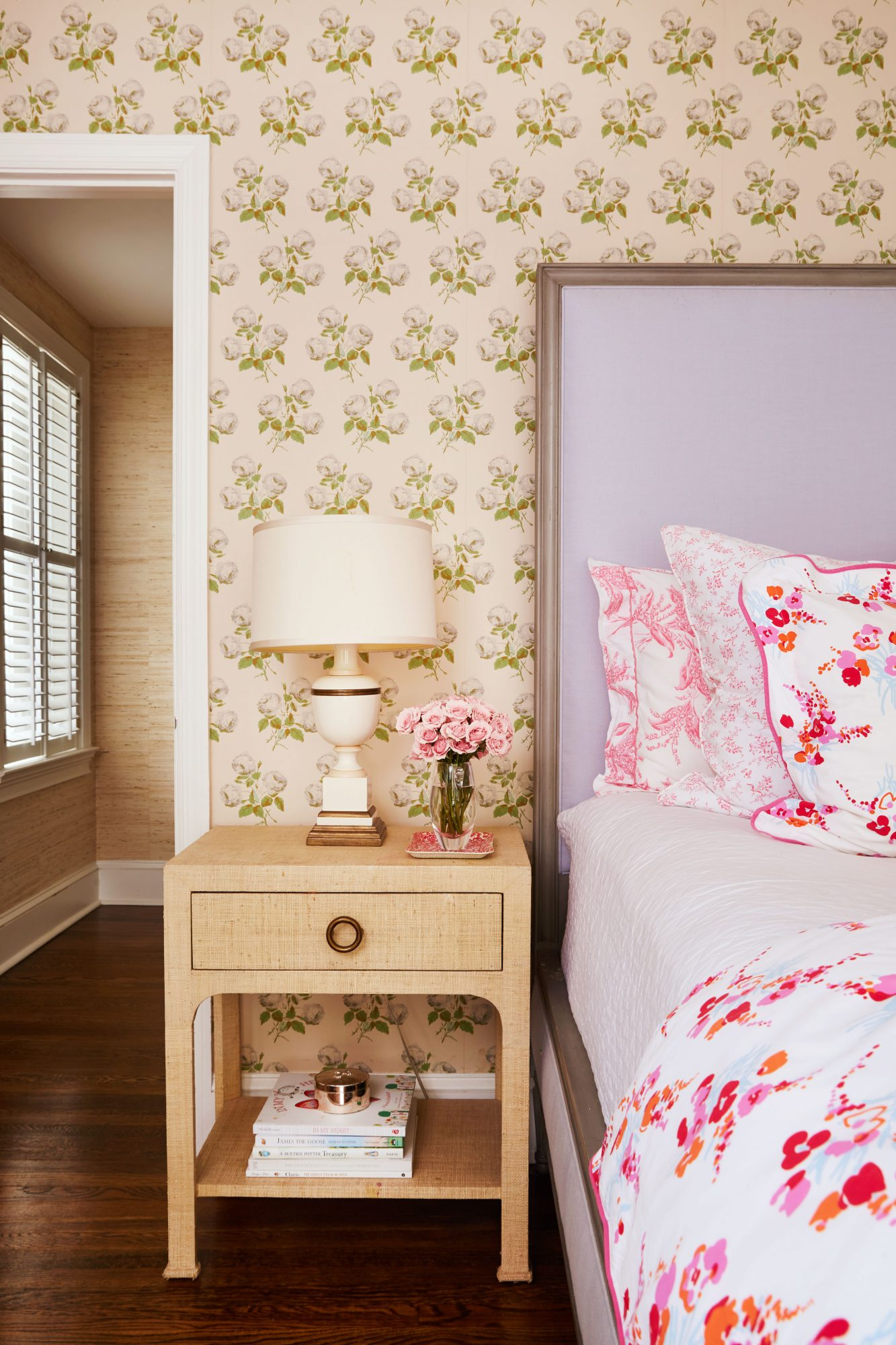 Young girl's bedroom with floral wallpaper, lavender upholstered bed, and pink bed linens