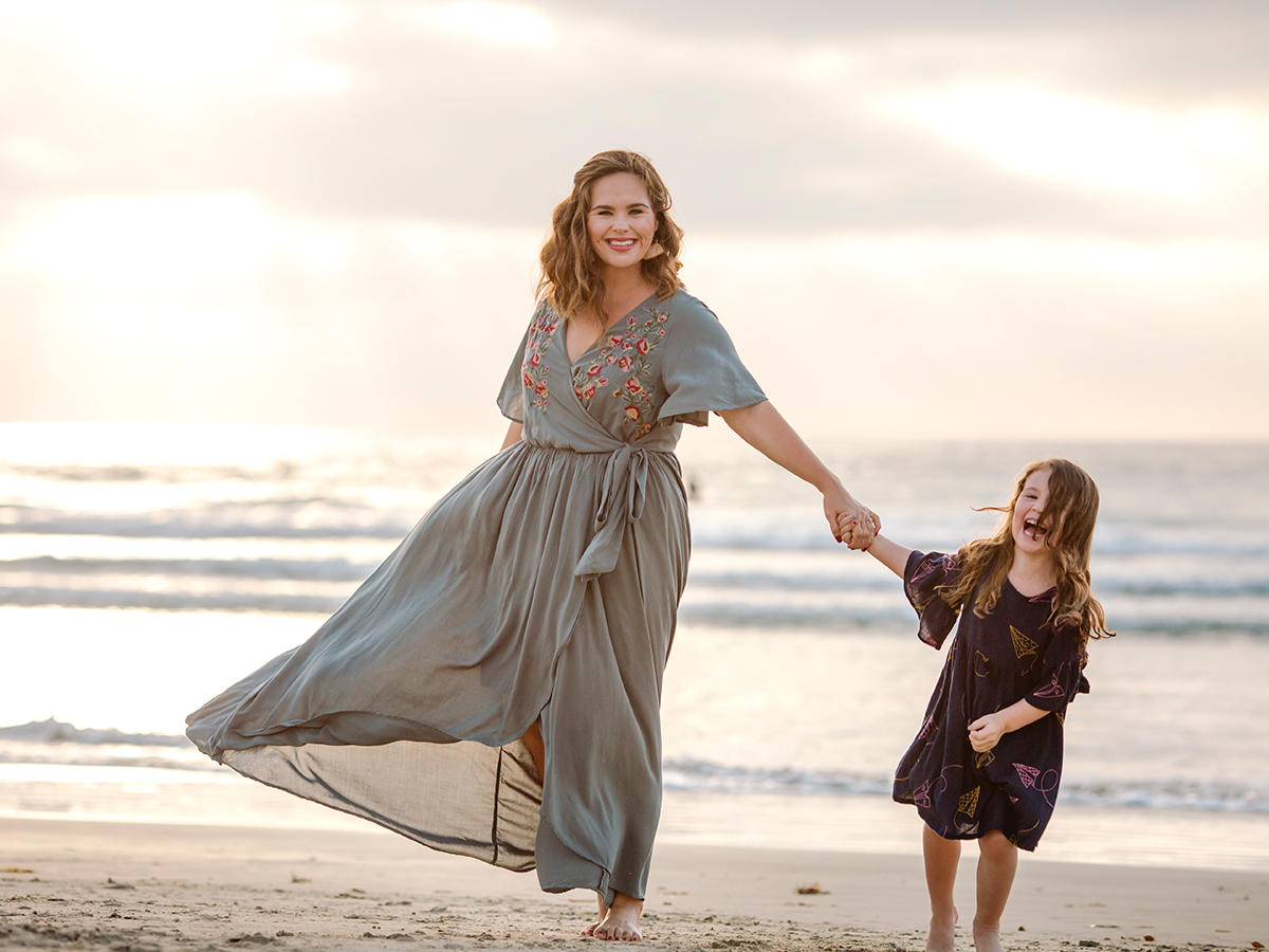 Beautiful mom in flowing dress walking on beach with 3 yr old daughter