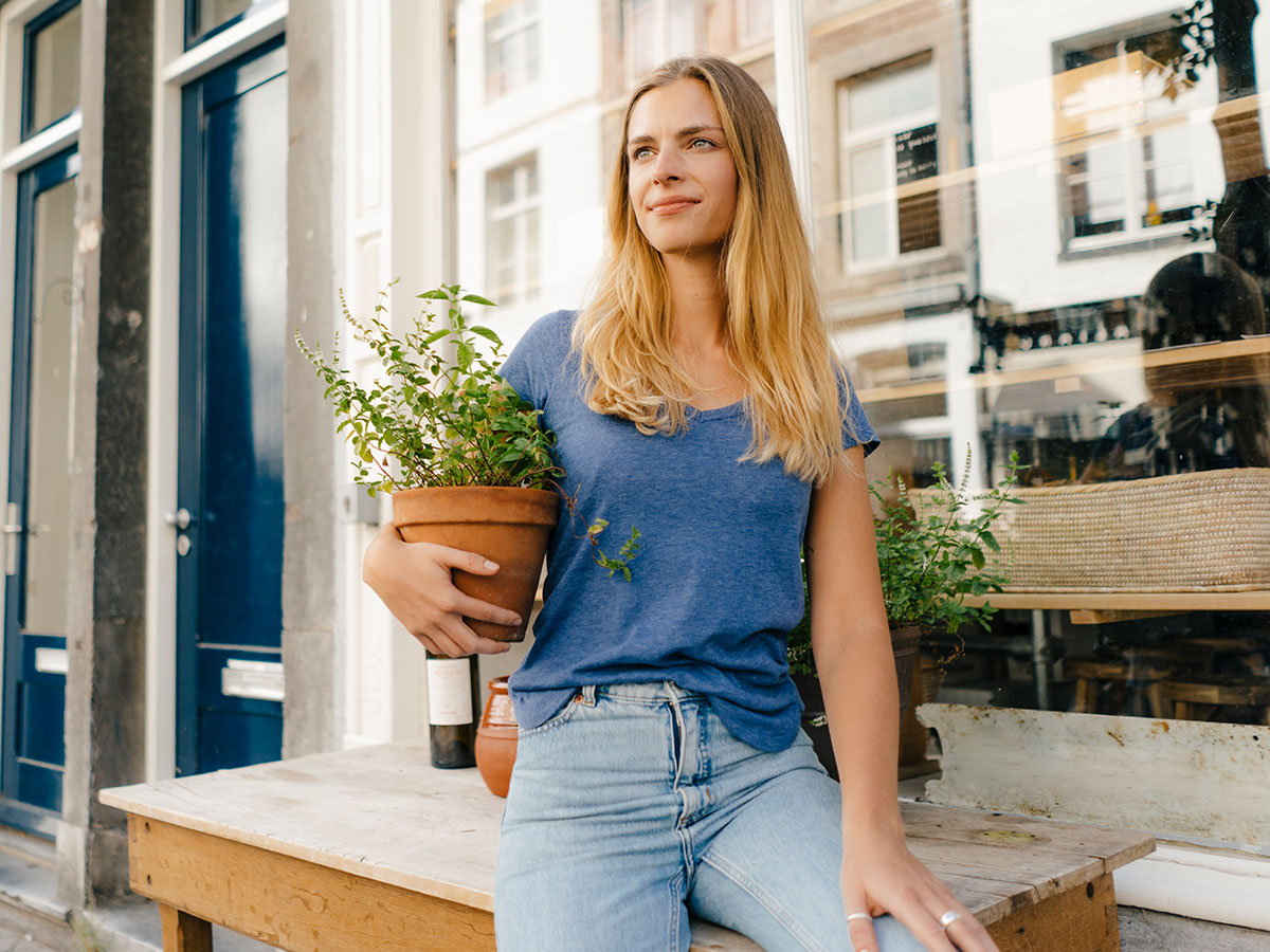 Netherlands, Maastricht, blond young woman holding flowerpot in the city