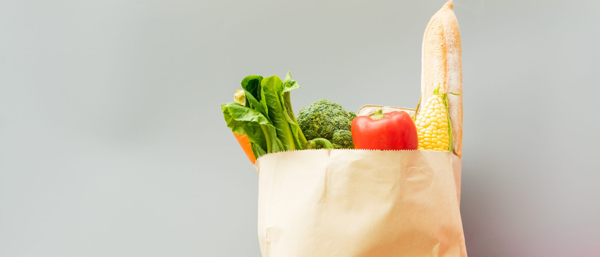 Close up paper bag full of groceries with fresh vegetables and fruit on grey background with copy space. Shopping concept