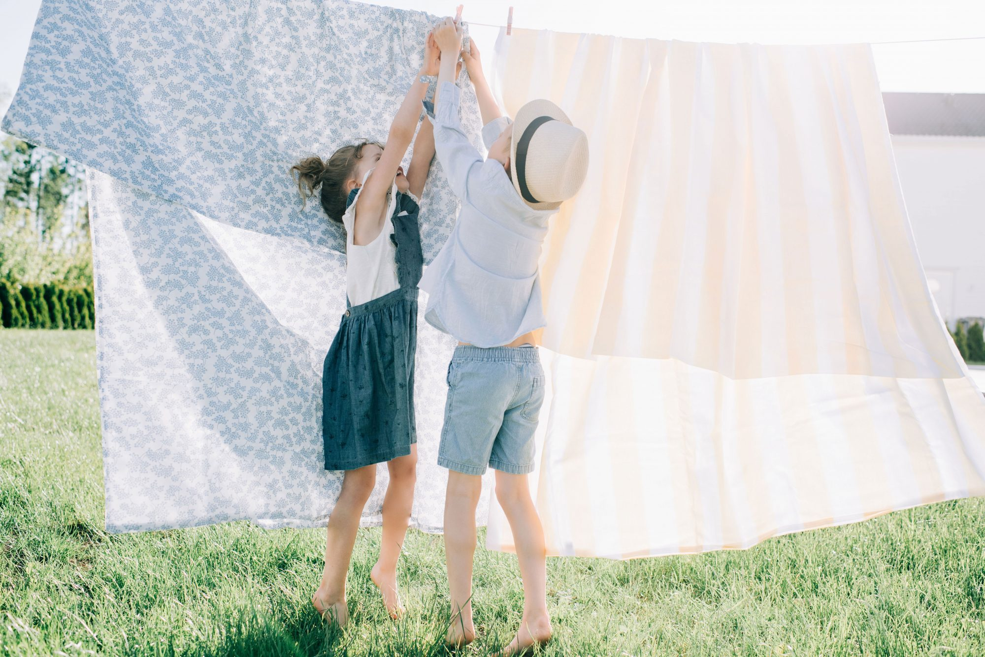 Two children hanging laundry on a clothesline