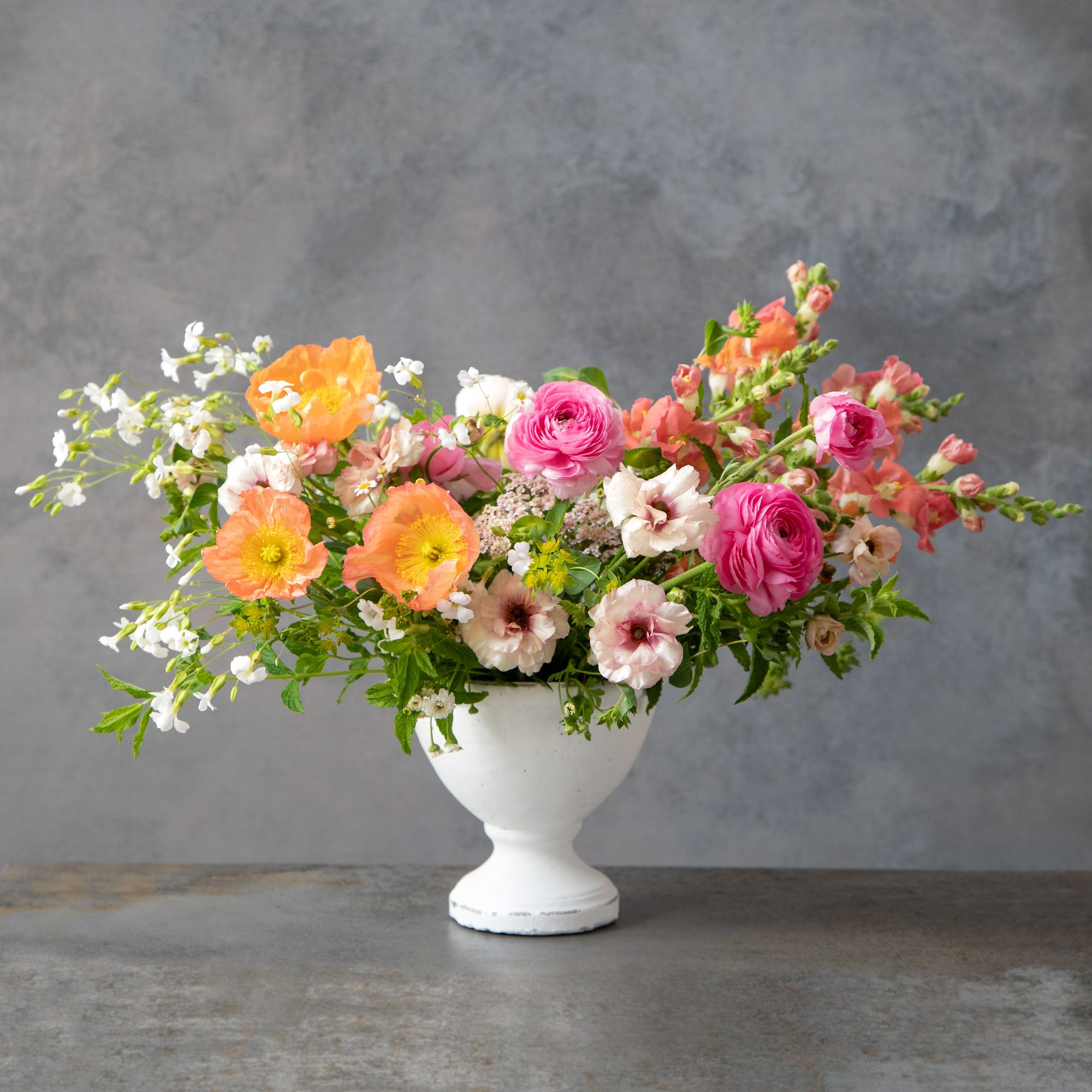 Spring Compote Flower Arrangement with Ranunculus, Snapdragons, and Poppies