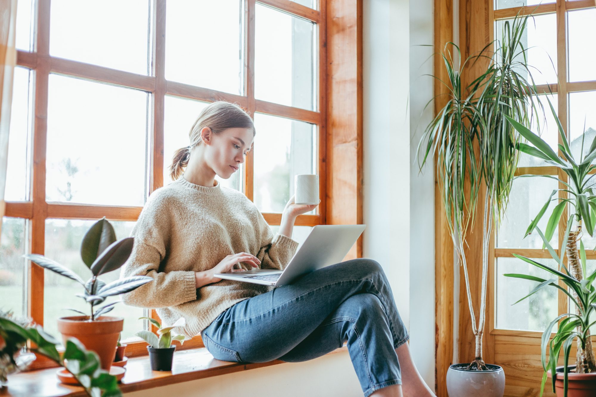 Candid portrait of woman drinking coffee with houseplants around