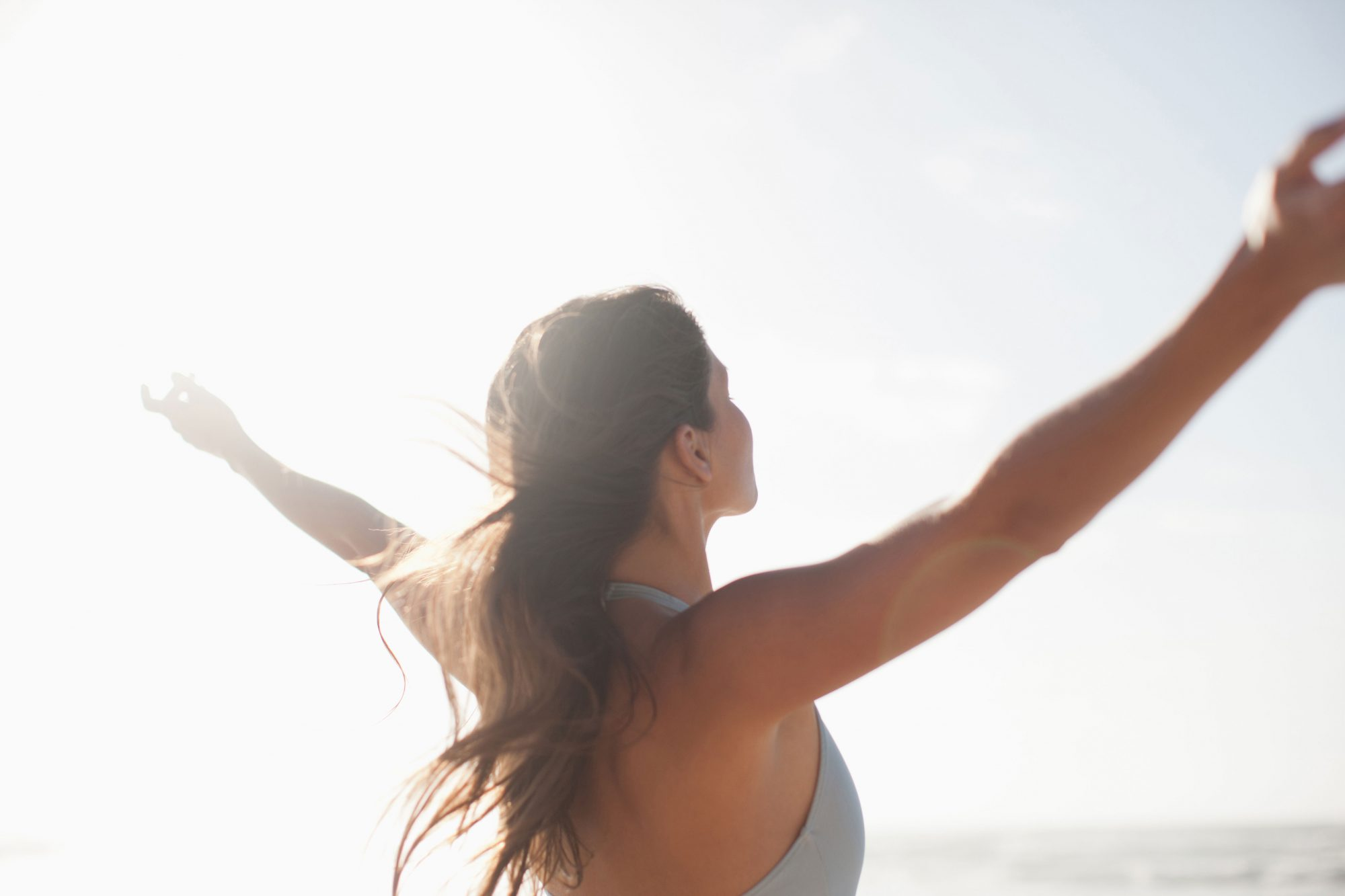 Woman with Arms Outstretched In Sun
