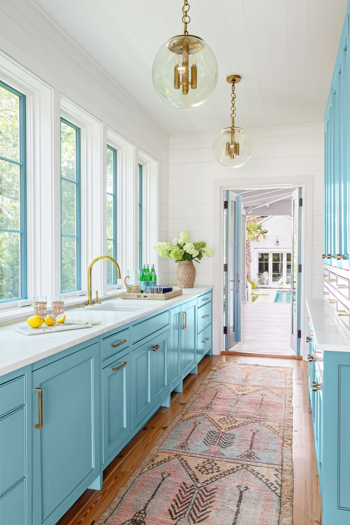 Galley kitchen with blue cabinetry and white walls