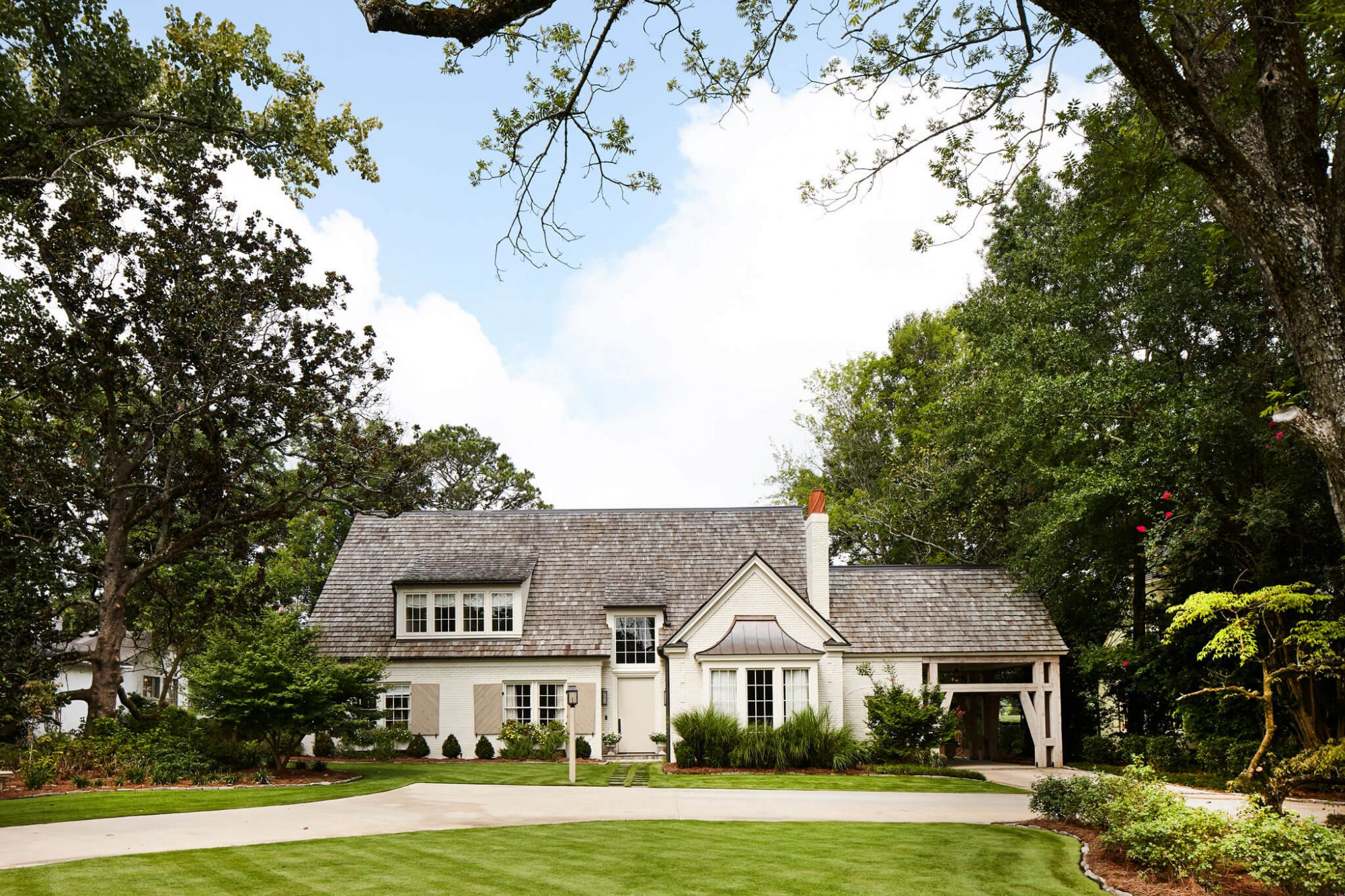 Converted farmhouse with shingled roof features a neutral color palette. Farrow and Ball's Stony Brick was used for the door, and archived color, Clunch, for the brick.