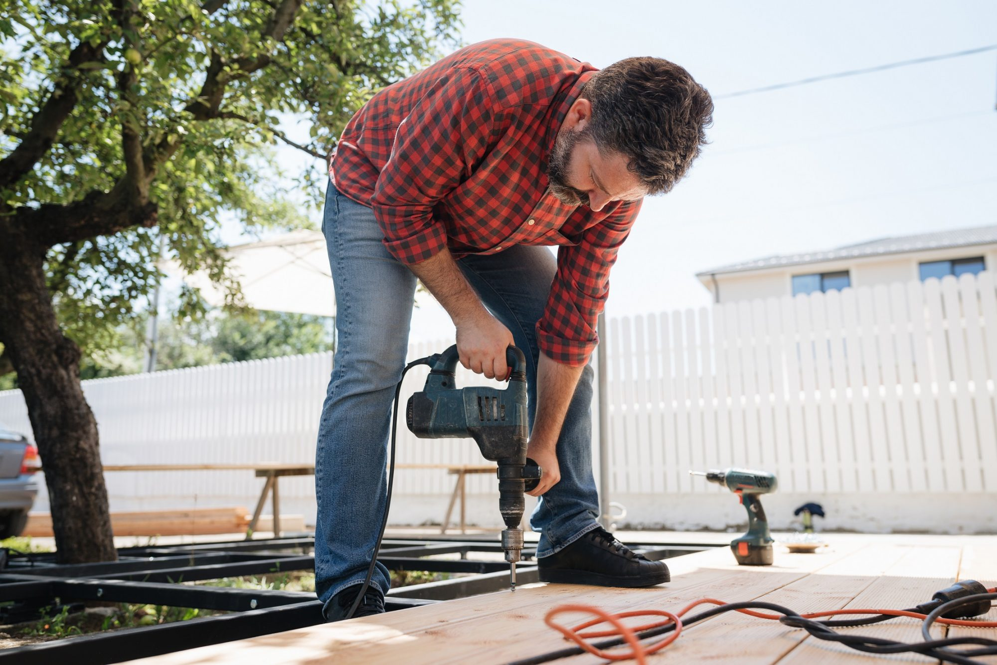 Carpenter installing a wood floor outdoor terrace in new house construction site