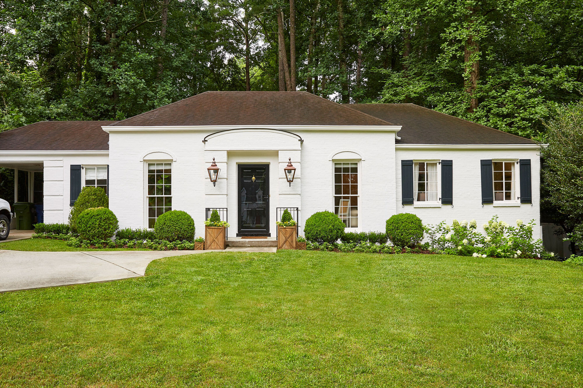 """White ranch-style house with Greek and Romanesque influence with a sloping roof. The door is painted in Farrow and Ball's """"Railings"""" shade."""