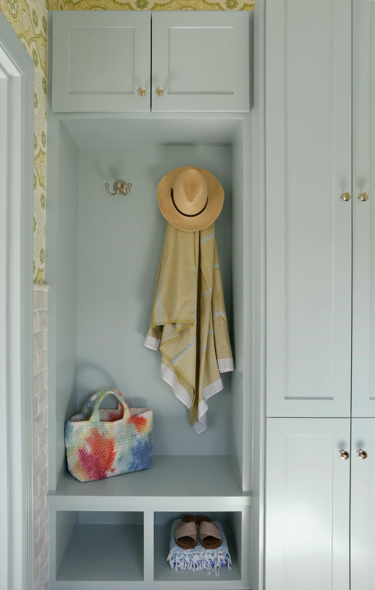 """Home entryway where a sunhat and shawl hang on a gold hook. Wall and cabinets are pained in Benjamin Moore's """"Woodlawn Blue"""" shade."""