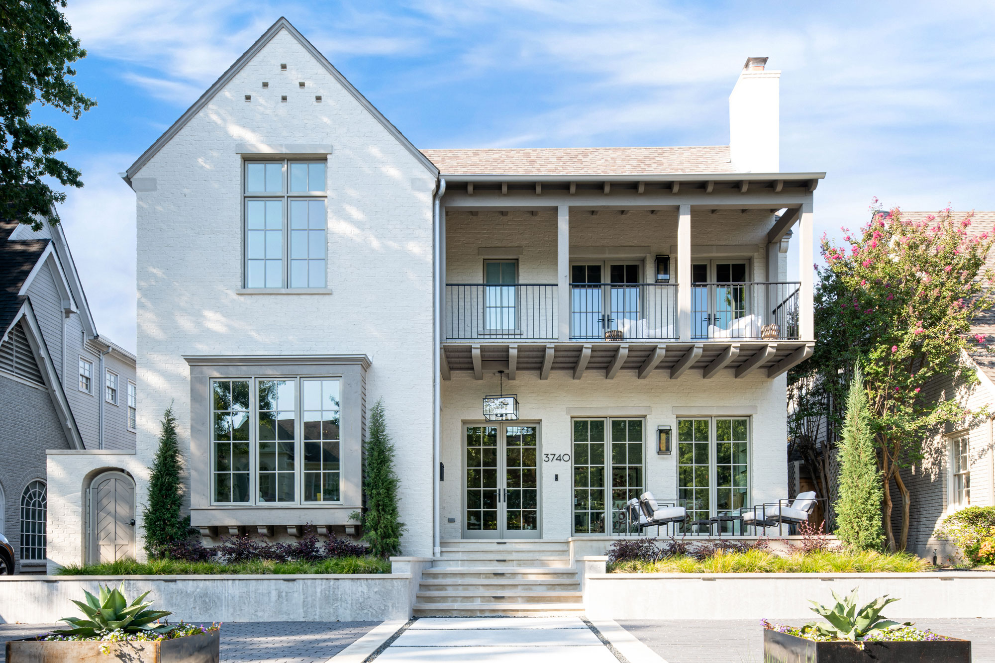 Two-story home with a balcony and front porch. Front door painted a custom color.