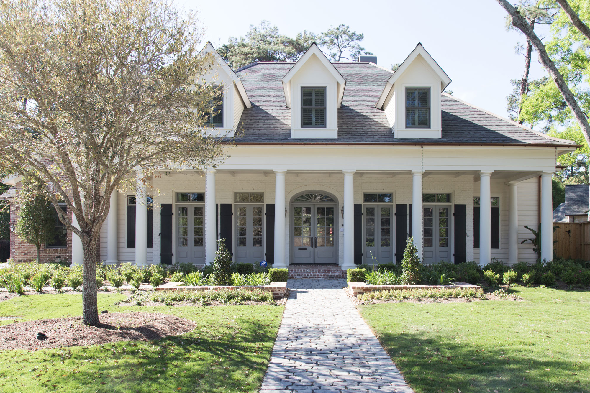"""Colonia-style home featuring front doors painted in Benjamin Moore's """"Cape May Cobblestone"""" shade."""