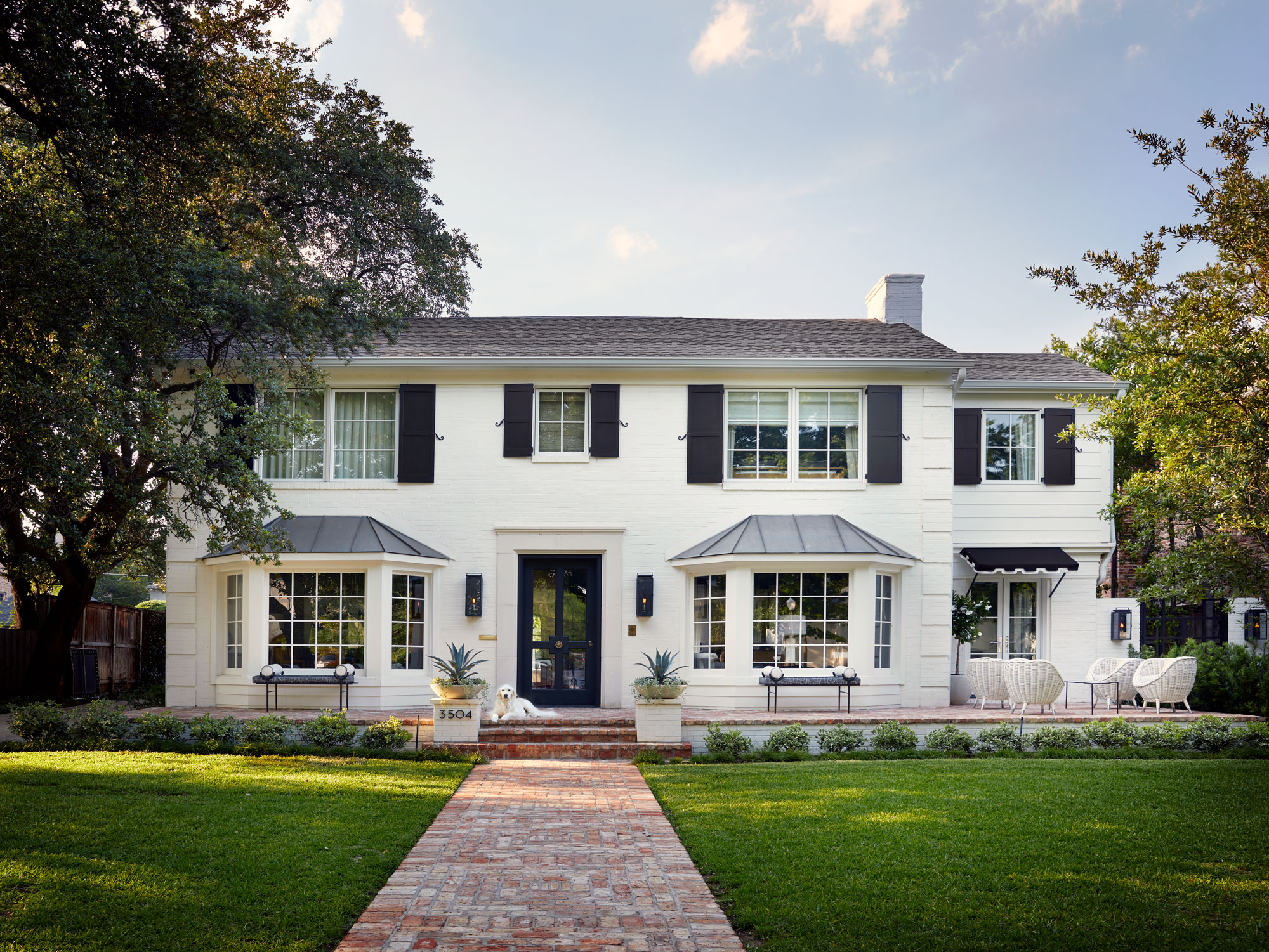 """White colonial-style house with shutters and a green lawn. The door is painted the Sherwin Williams shade of """"Tricorn Black."""""""