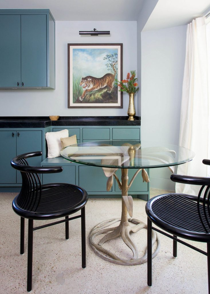 White dining room with periwinkle cabinets and mid century dining chairs.