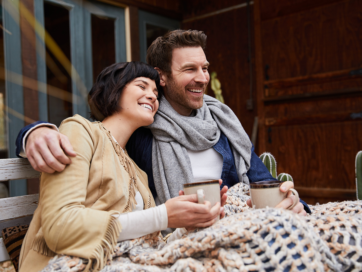 Laughing couple drinking coffee on a bench outside on a cool morning