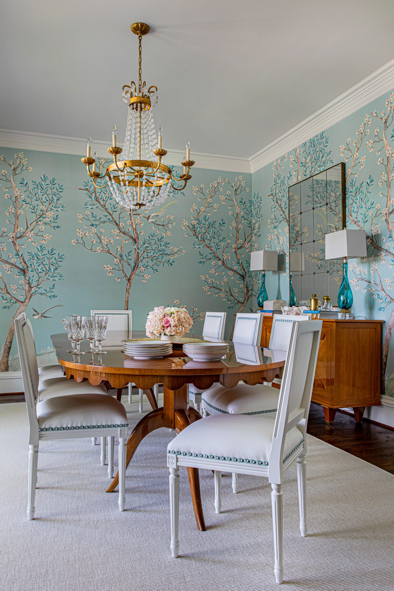 Dining Room with Oval Table, Blue Floral Mural, and Gold Crystal Chandelier