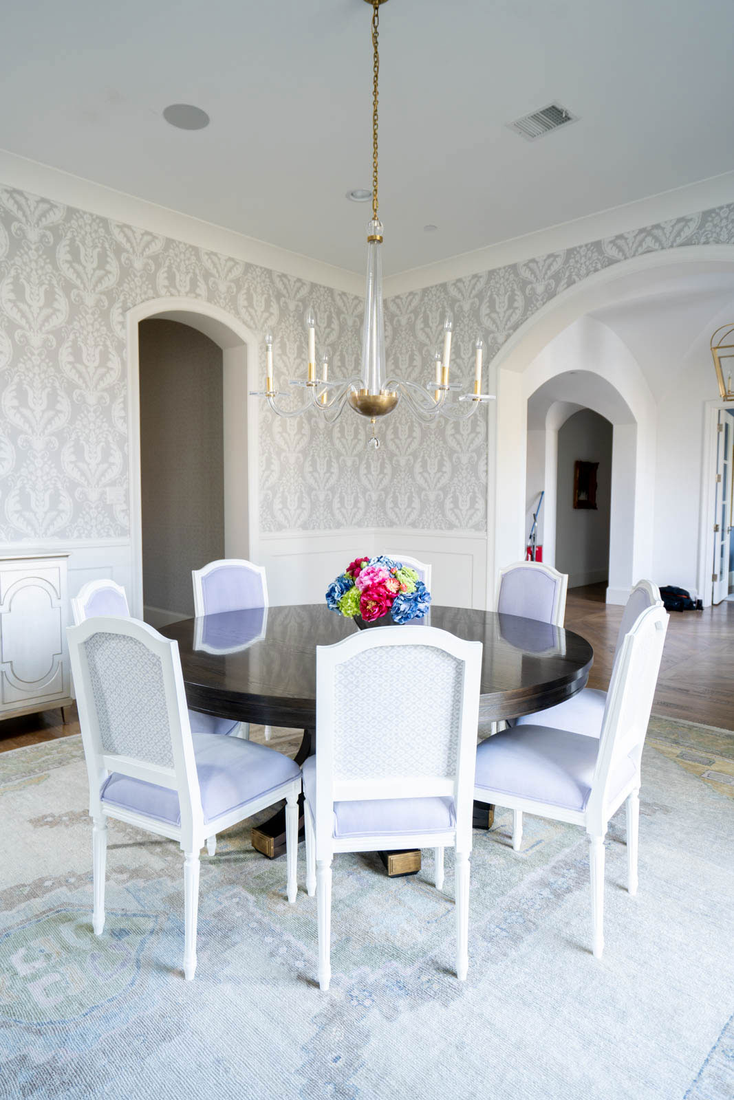 Wallpapered Dining Room with Round Table and Upholstered Chairs