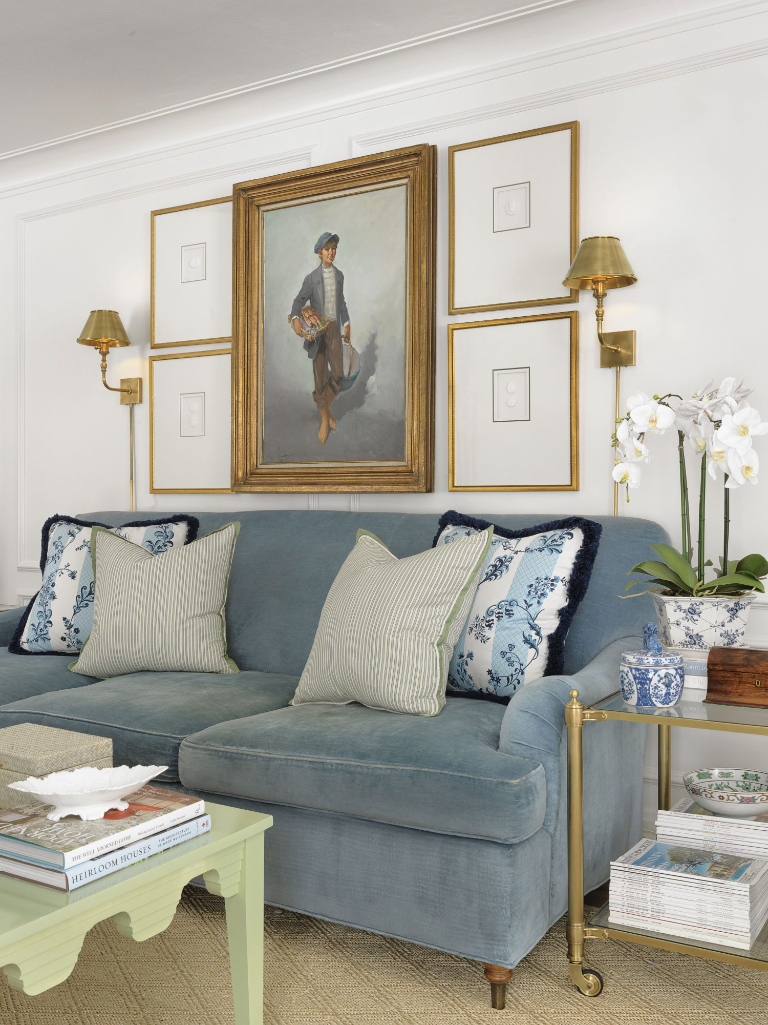 Living Room with Blue Velvet Couch, Gold Sconces, and Orchid
