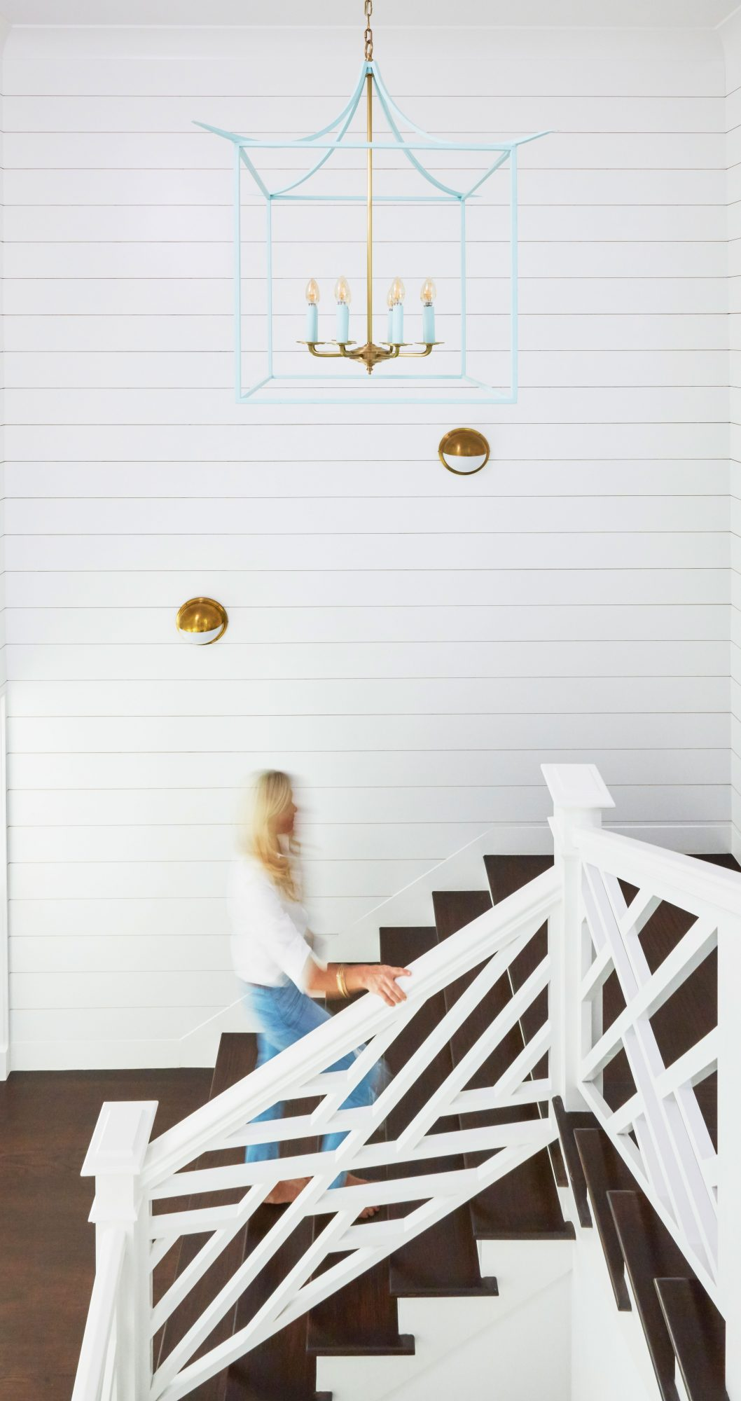 Staircase with White Wood Paneled Wall and Gold Light Fixtures