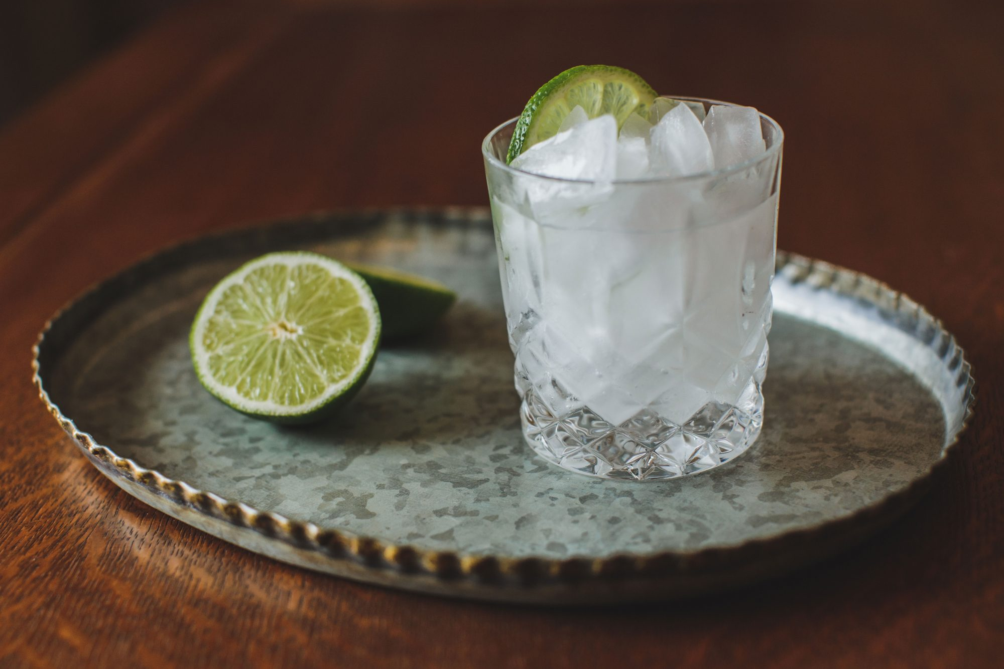 Cocktail Sitting on a Tray with Limes