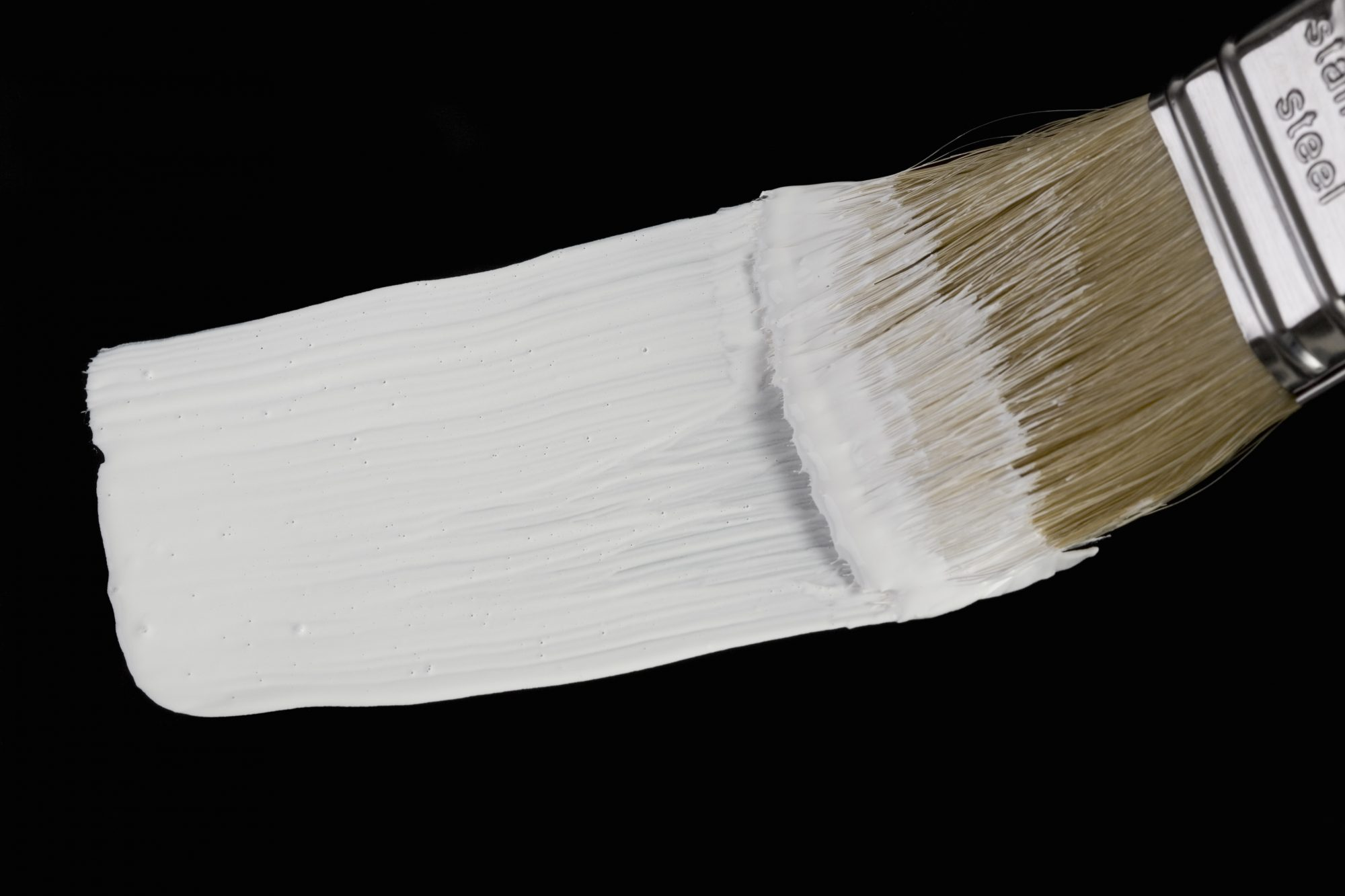 A paintbrush painting a white stripe