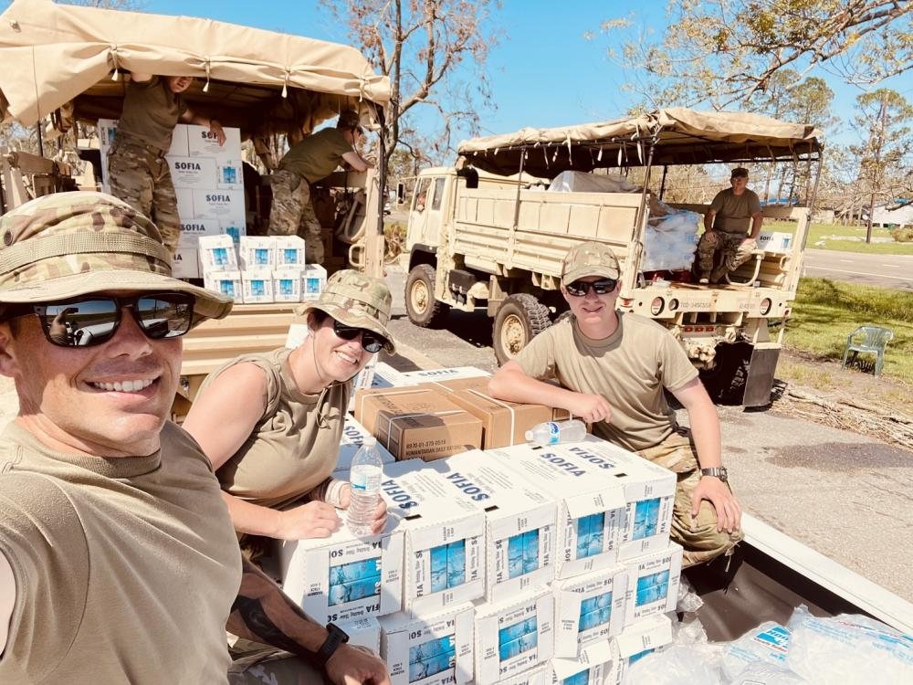 Oklahoma Air National Guard Staff Sgt. Macey Winegarner (center) helps distribute water to residents affected by Hurricane Ida in Louisiana